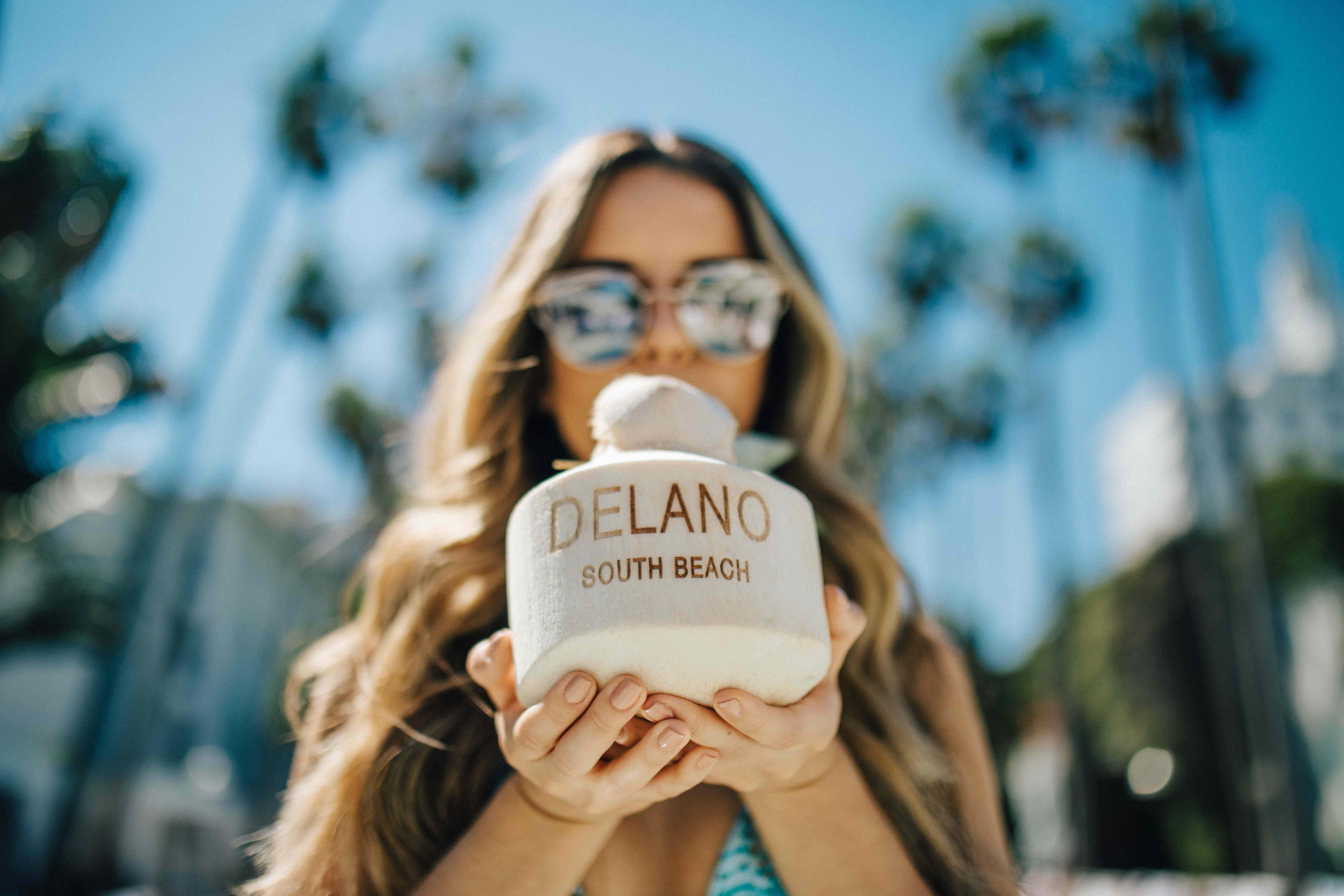 woman drinks out of coconut that says Delano South Beach