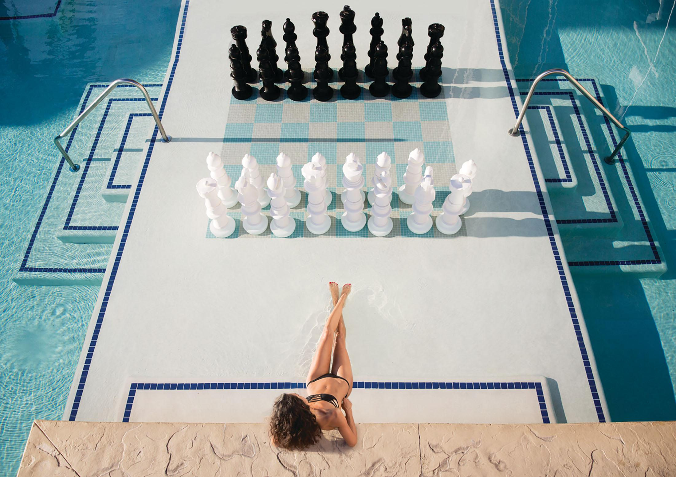 Woman sits in a pool in front of a giant chess set
