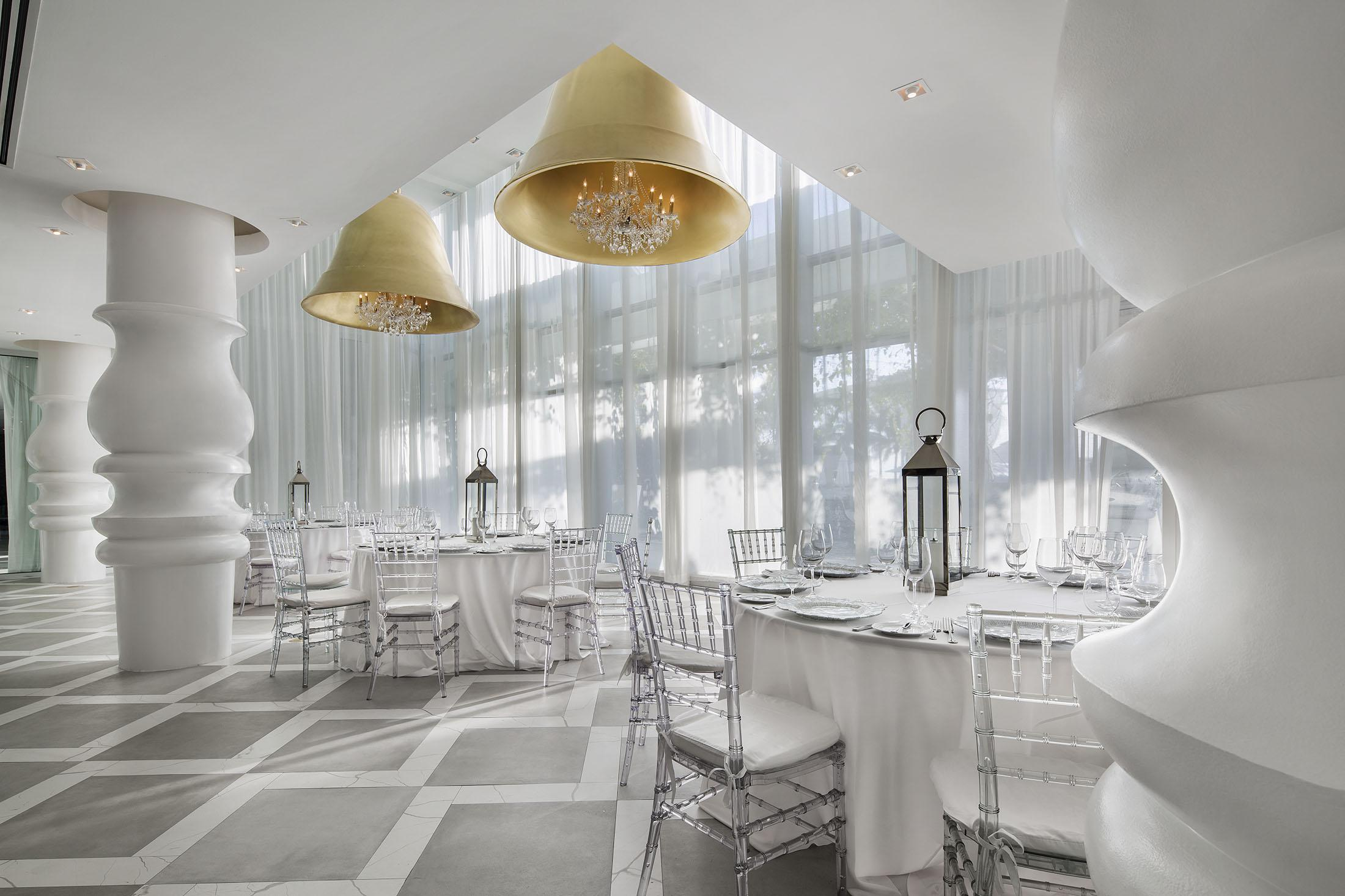 Tables and chairs set up for an event in a white room.