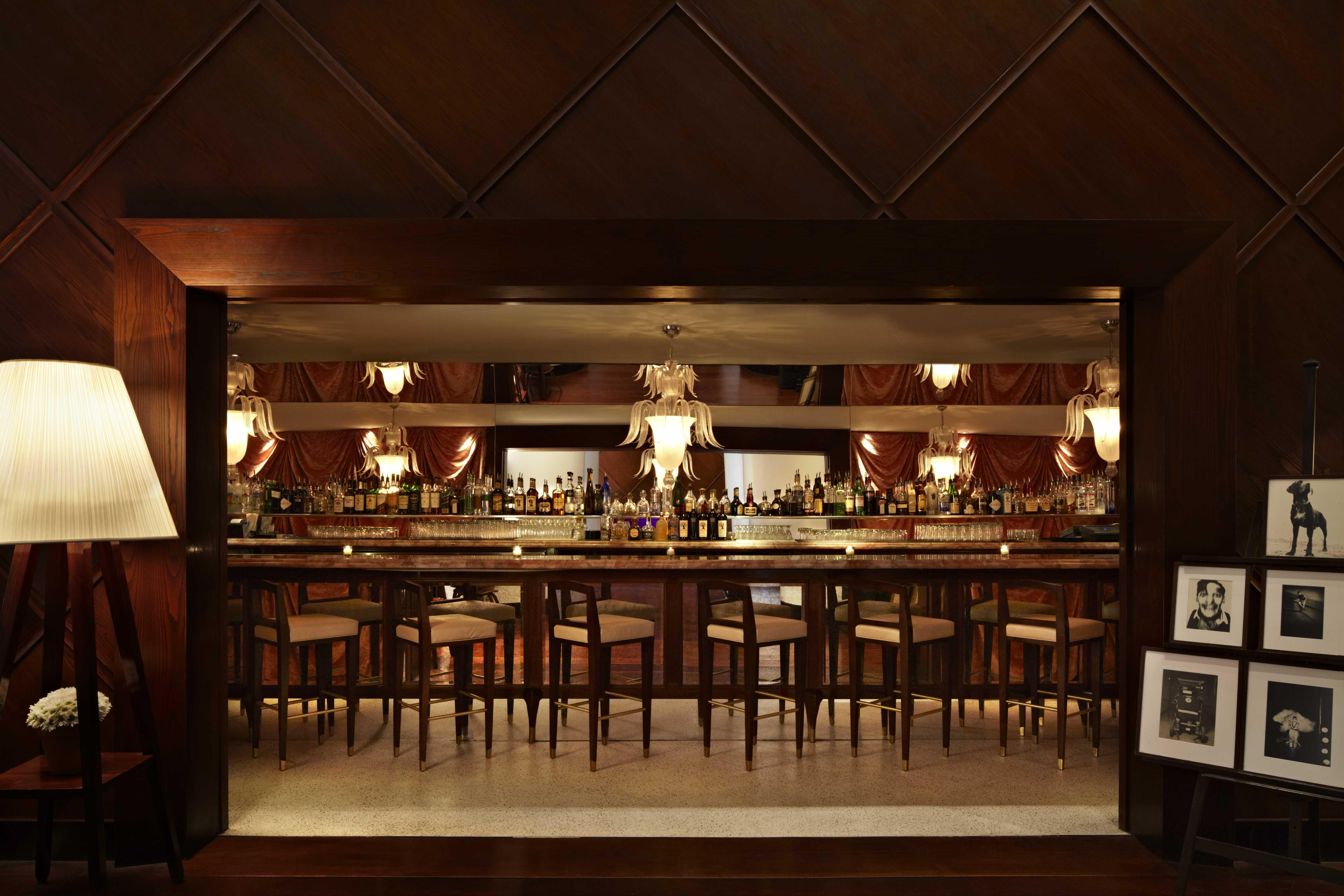 chairs in front of a softly lit wooden bar