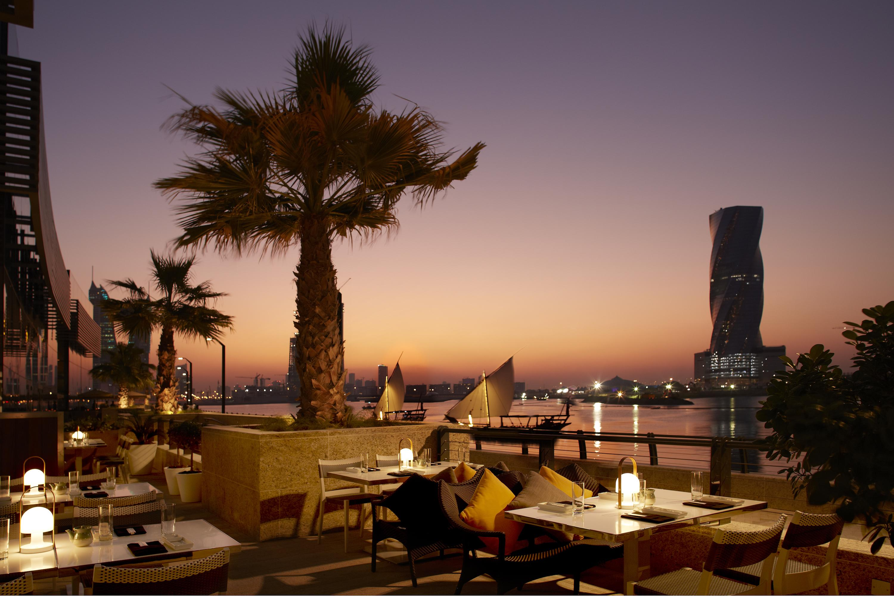 katsuya bahrain patio overlooking the ocean with palm trees and candle lit tables