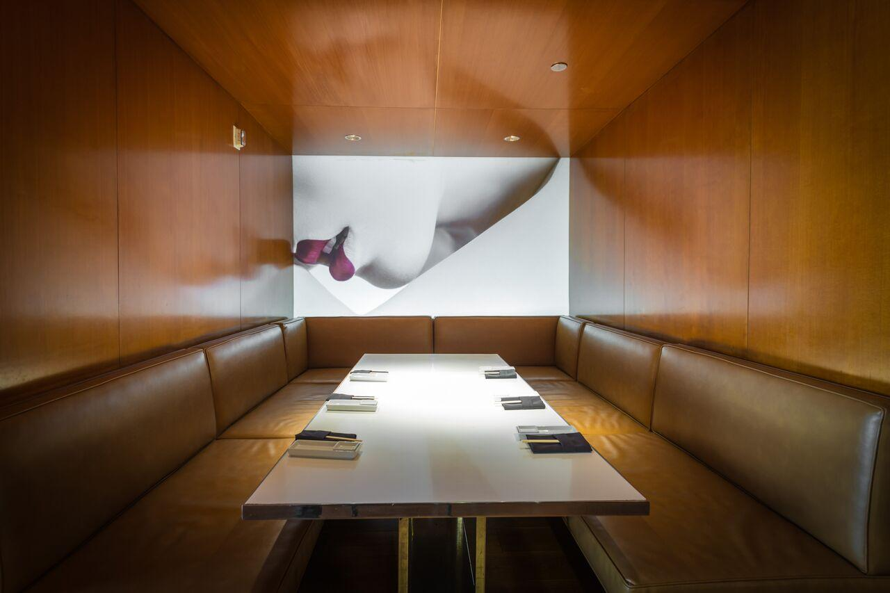 private dining rom with wooden walls, leather booths featuring a mural of red lips
