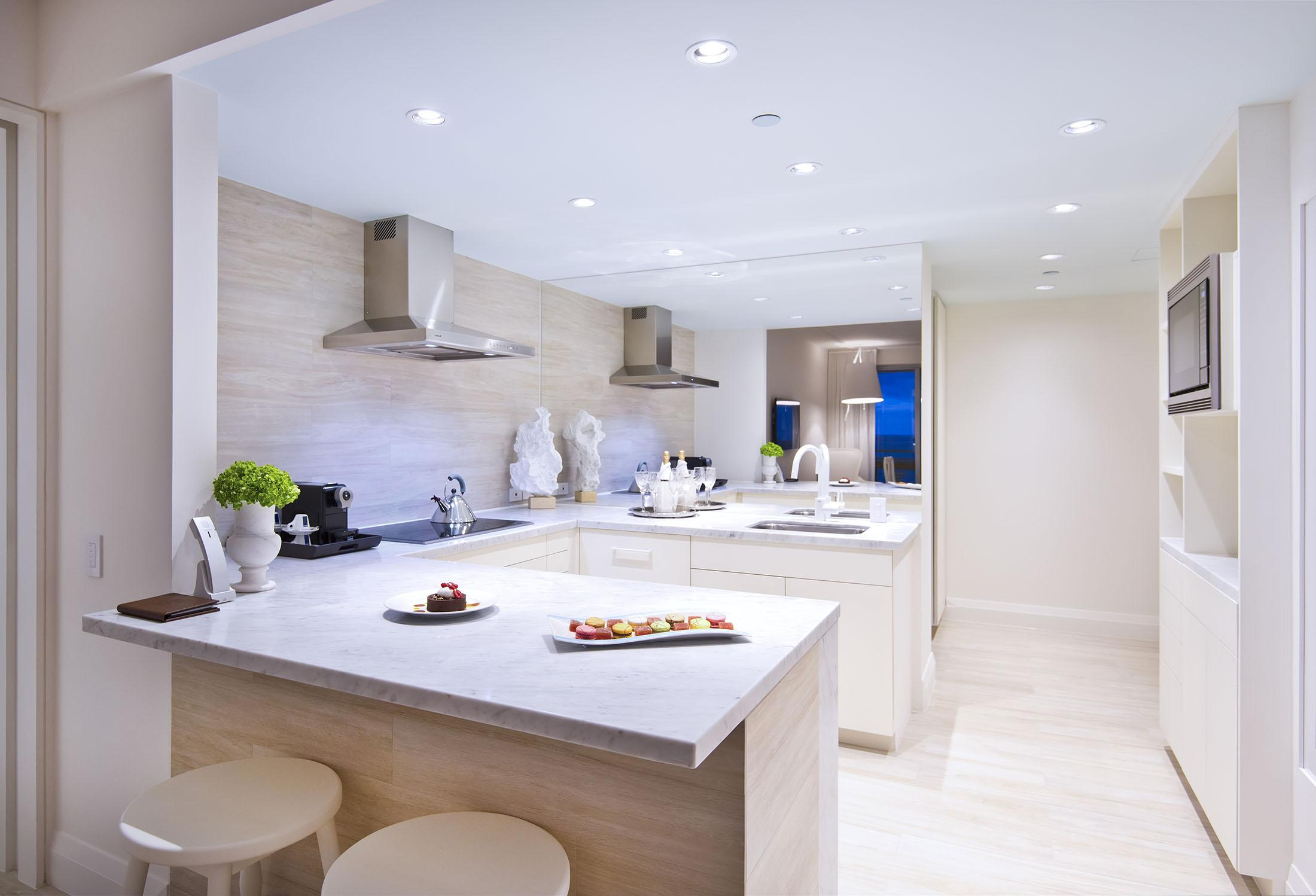 A white kitchen with bar stools