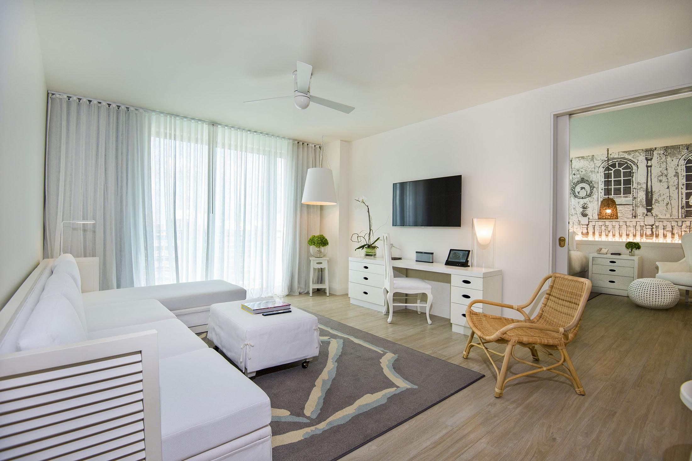 A living room for a hotel suite with a bedroom in the background.