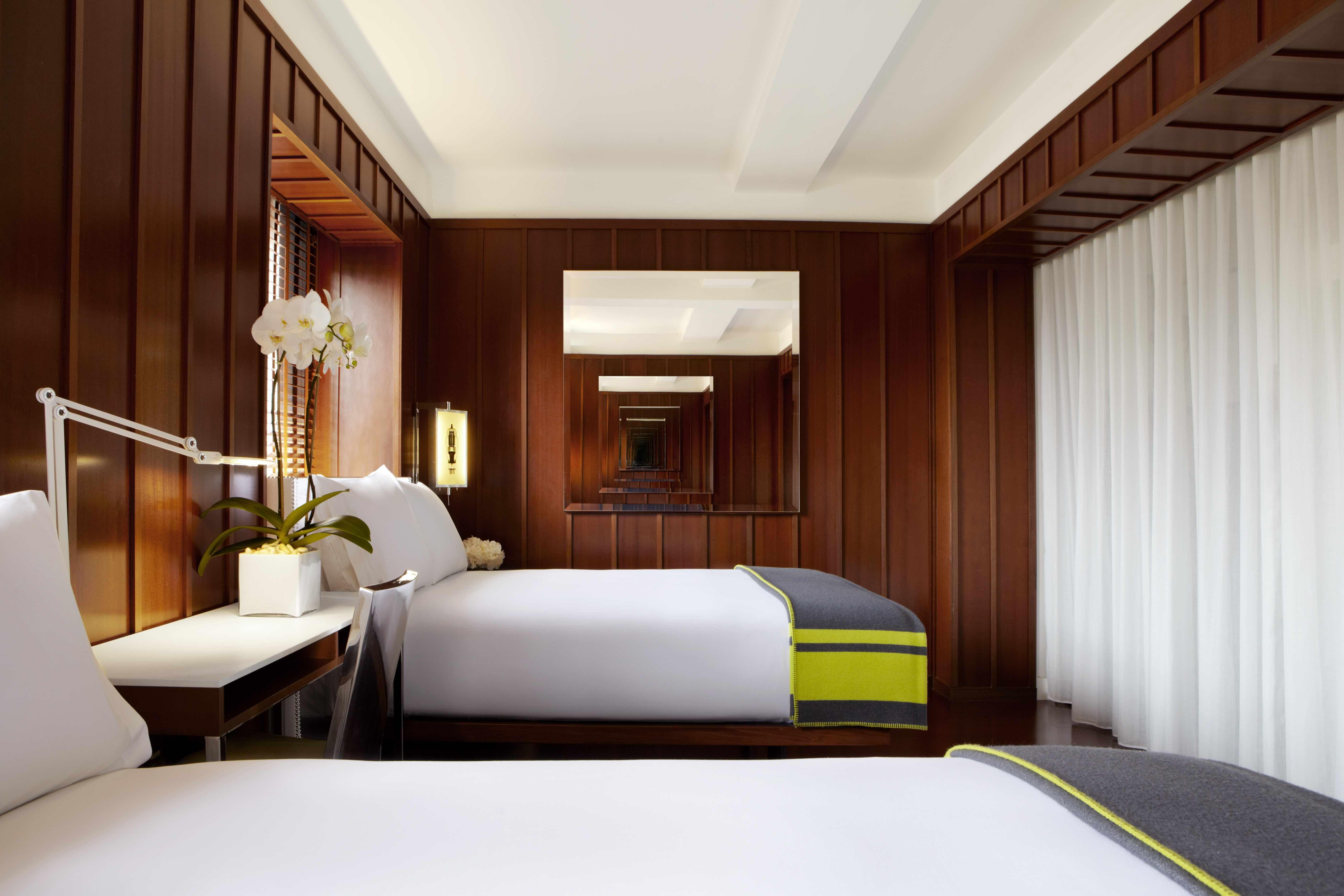hotel room with two double beds and dark wood walls