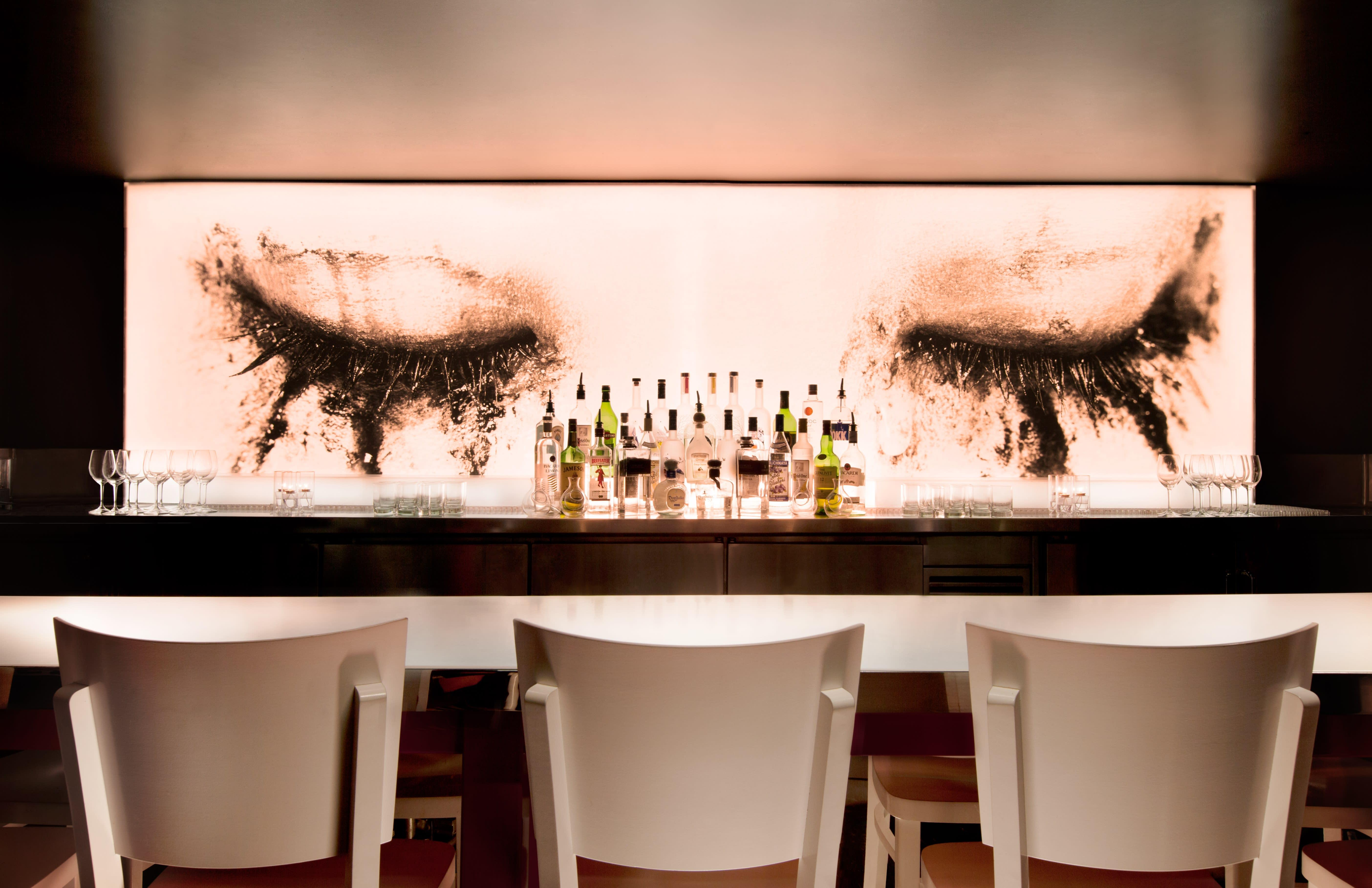 bar with three white chairs with liquor display and wall mural with eyes and smudged mascara