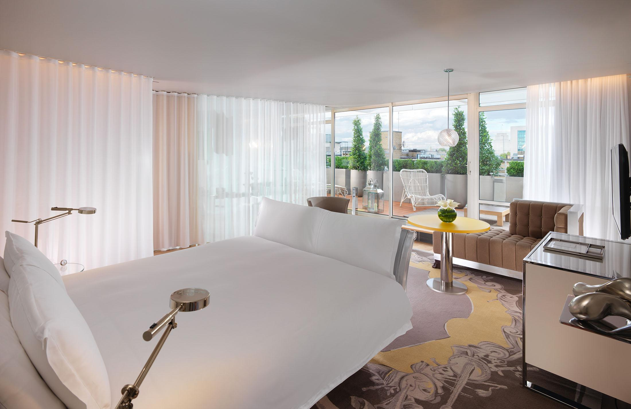 hotel room bed with white linens and terrace