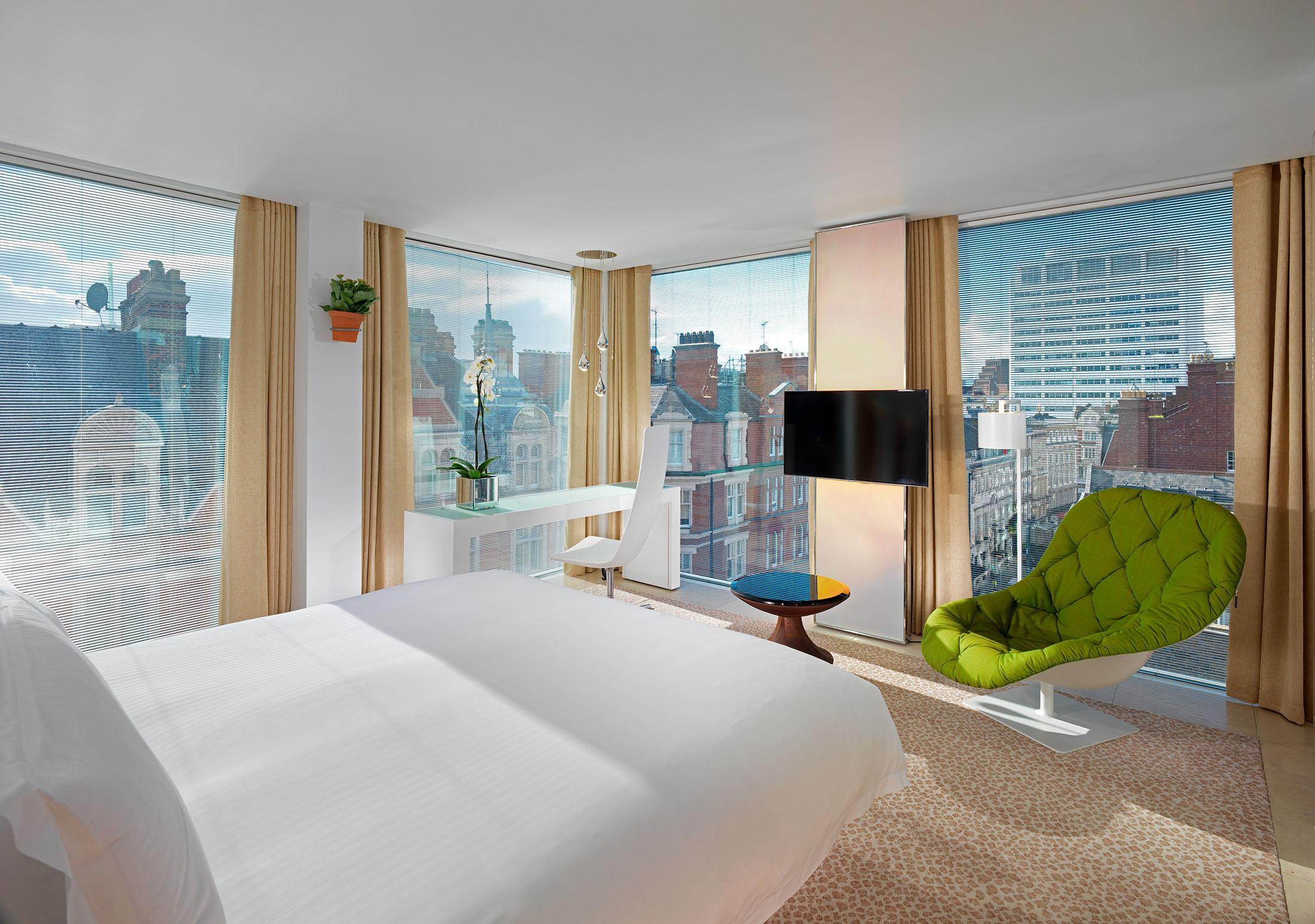 hotel bedroom with large windows overlooking city