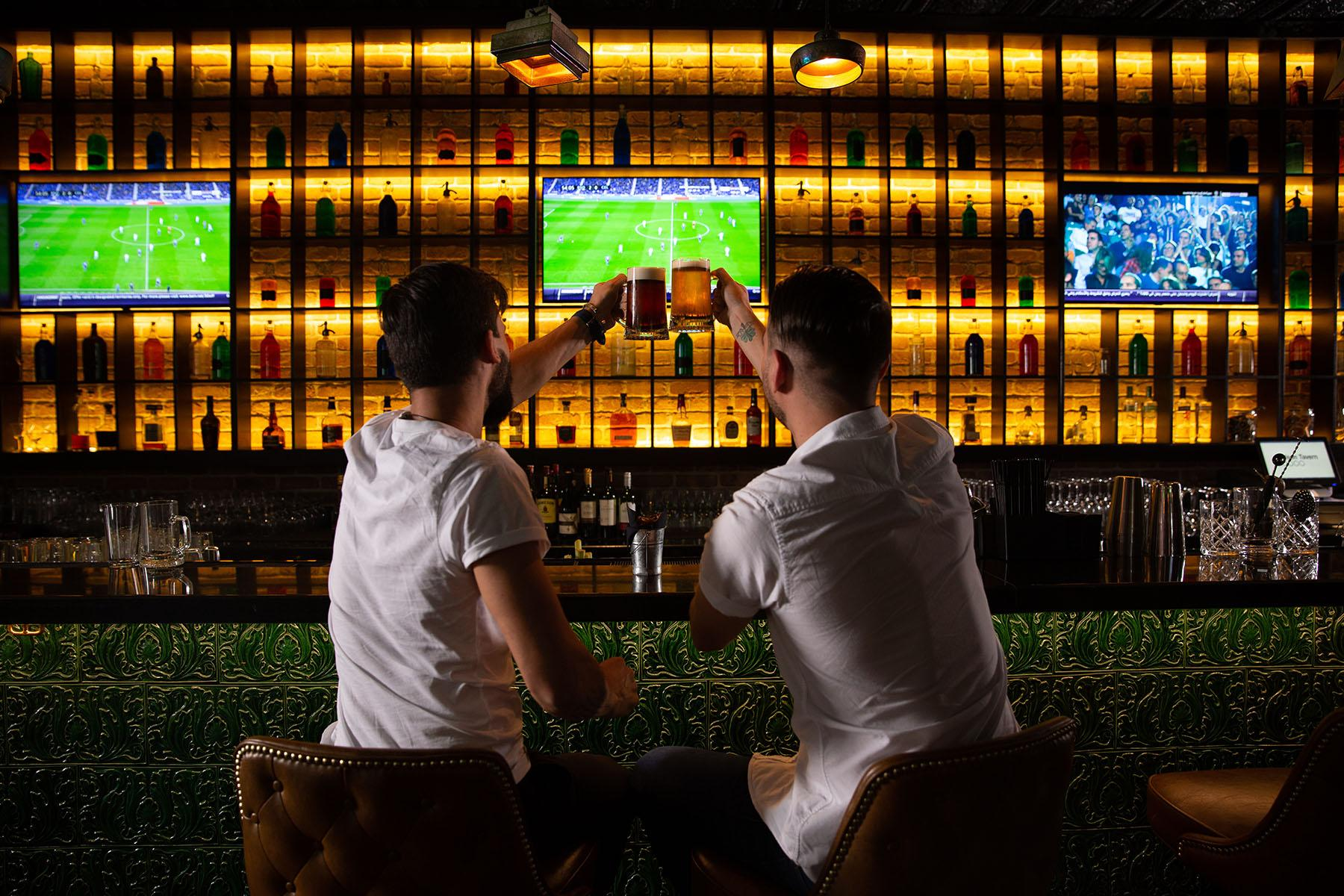 Men cheers at bar with soccer game on in background