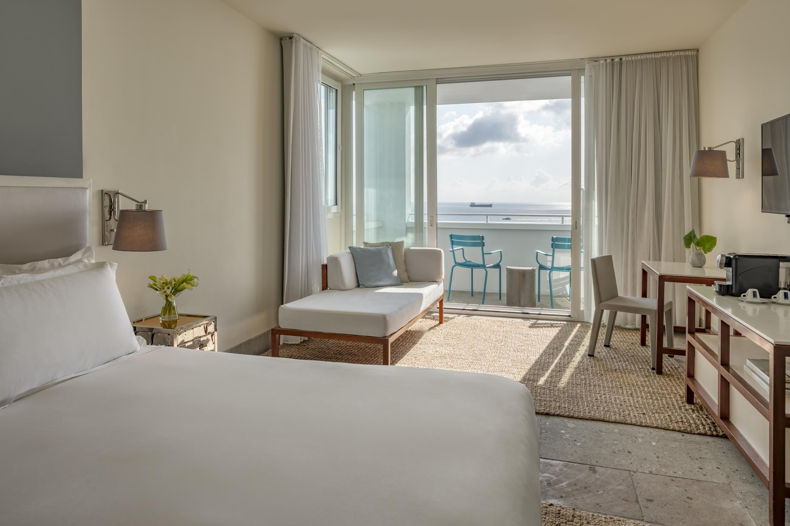 hotel room with bed and chaise lounge overlooking the ocean