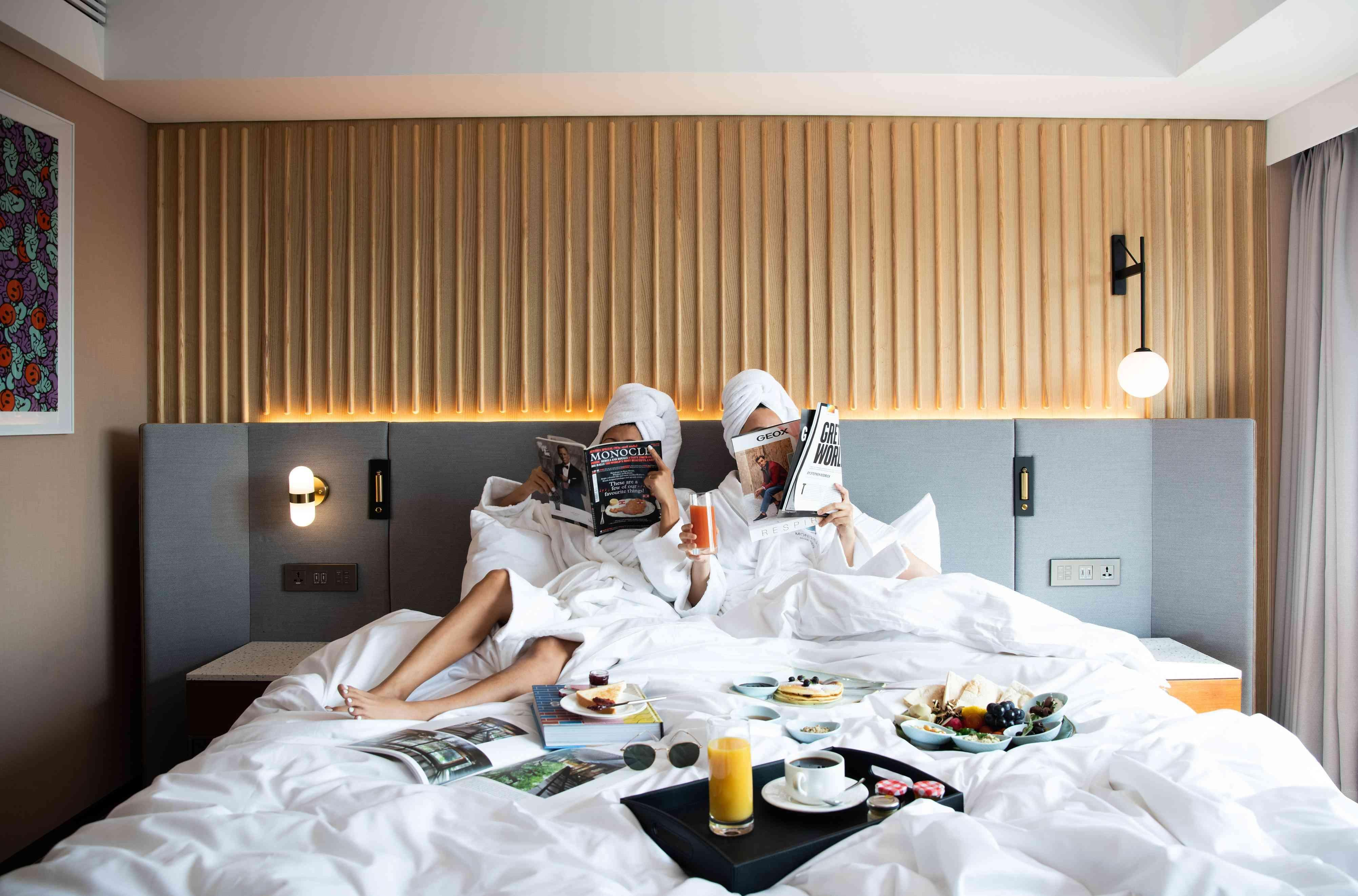 people on hotel bed with breakfast