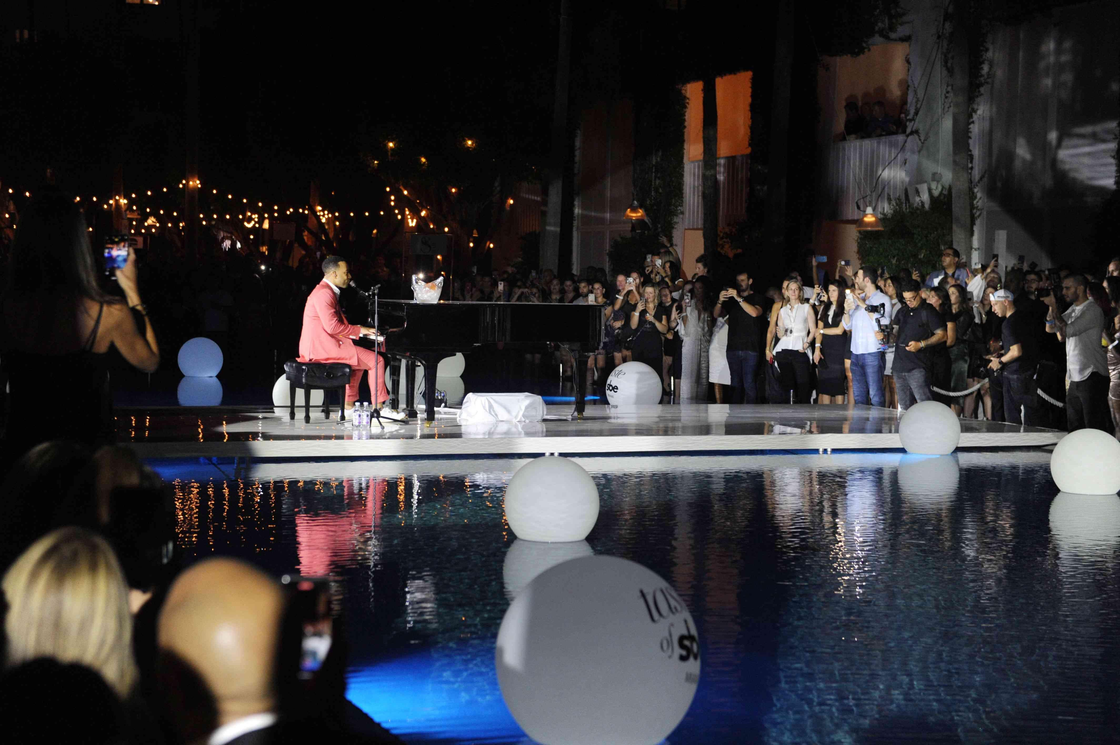 John Legend at a piano by a pool