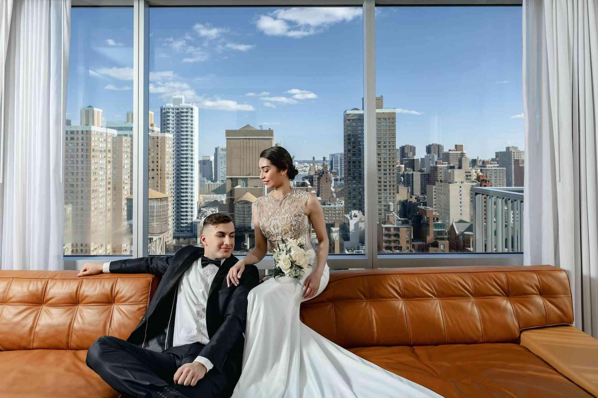 bridge and groom on a couch with NY view