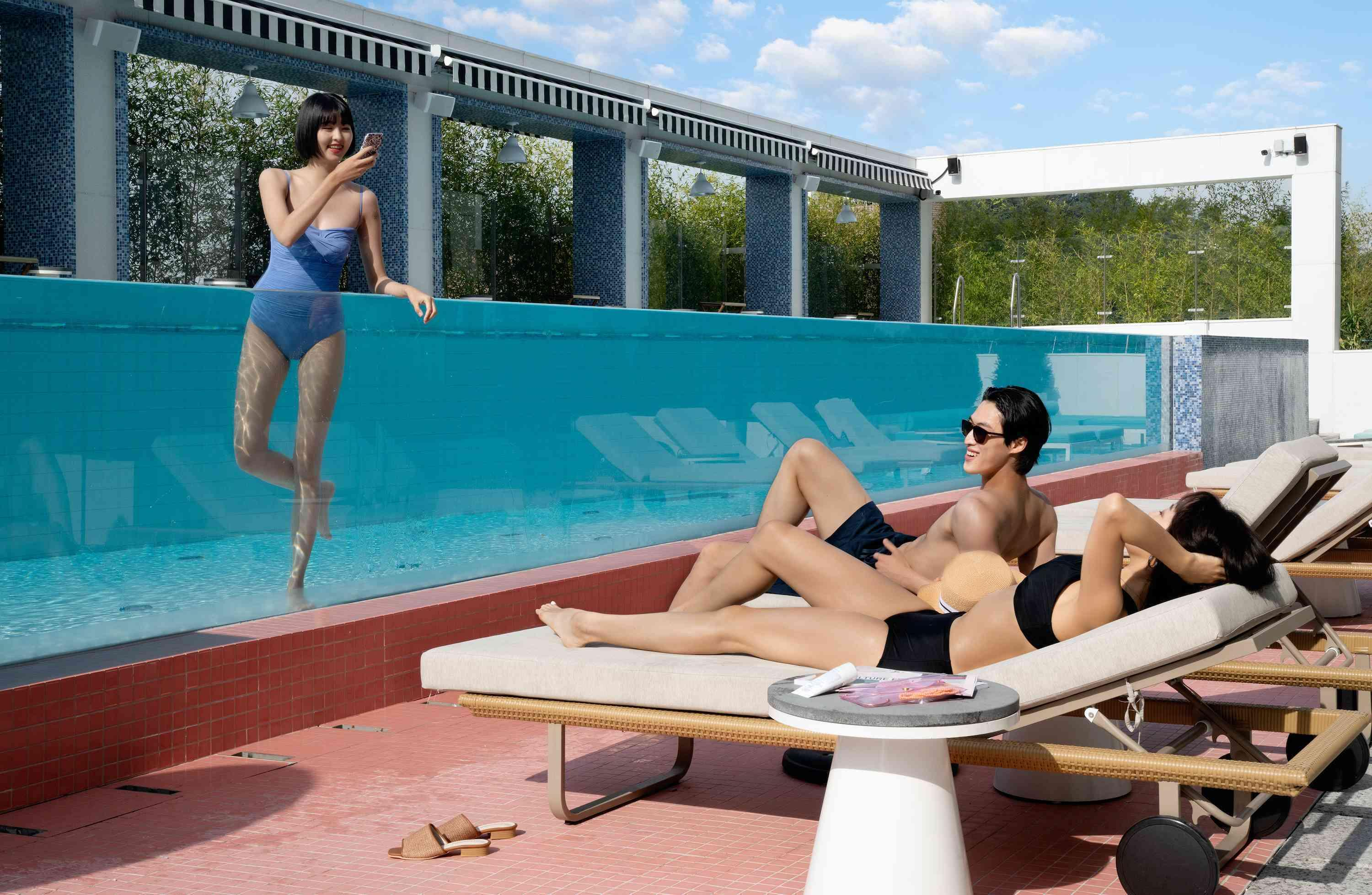 Woman in a pool, couple on loungers