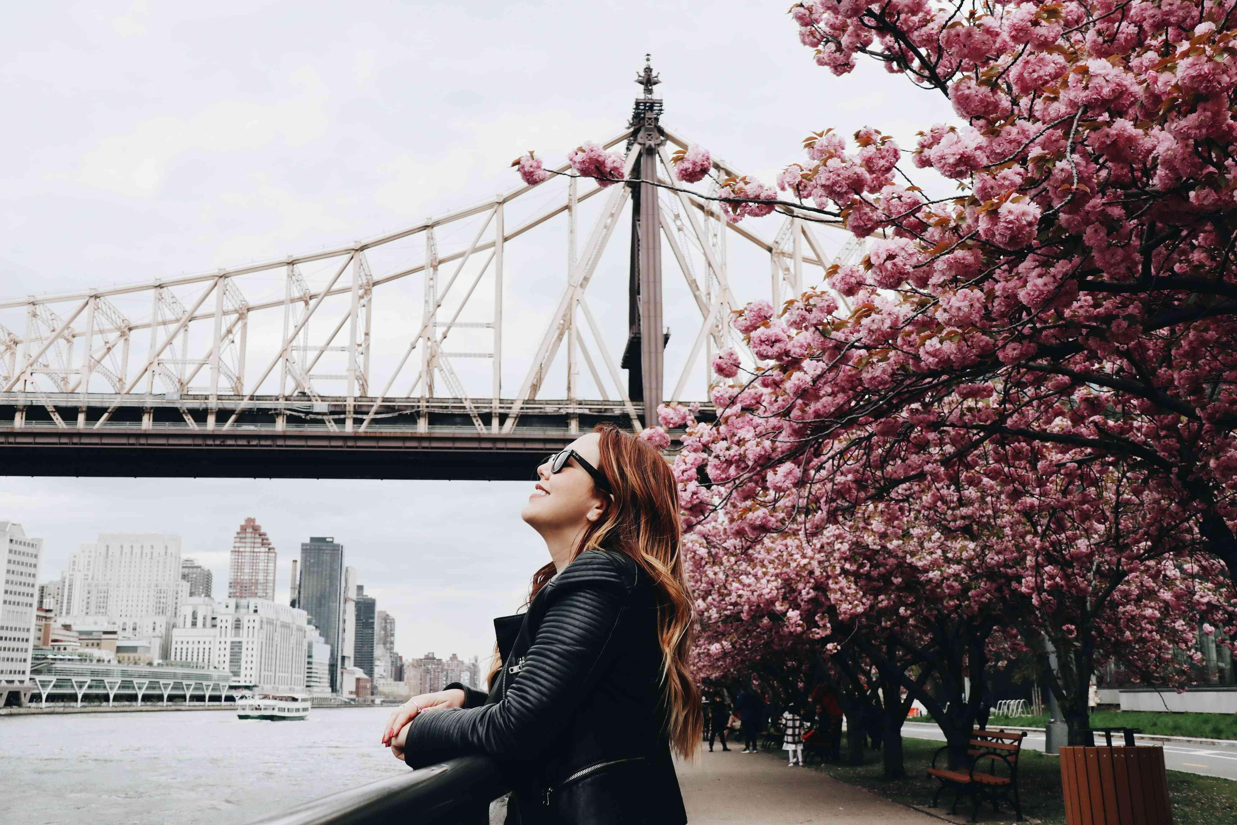 woman outside at the new york waterfront with spring blooms in the trees and a bridge in the background