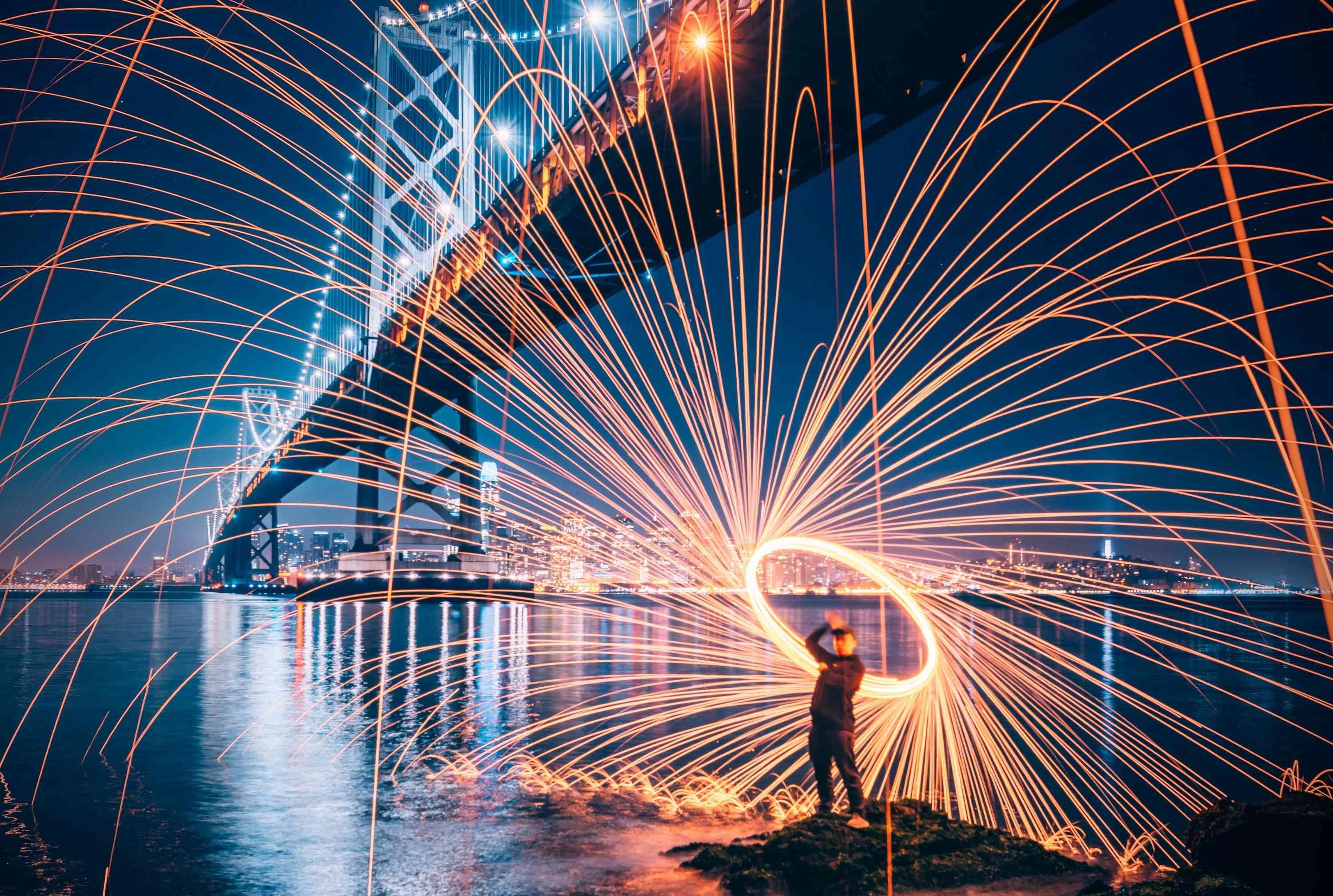 a man with fireworks by a NY bridge