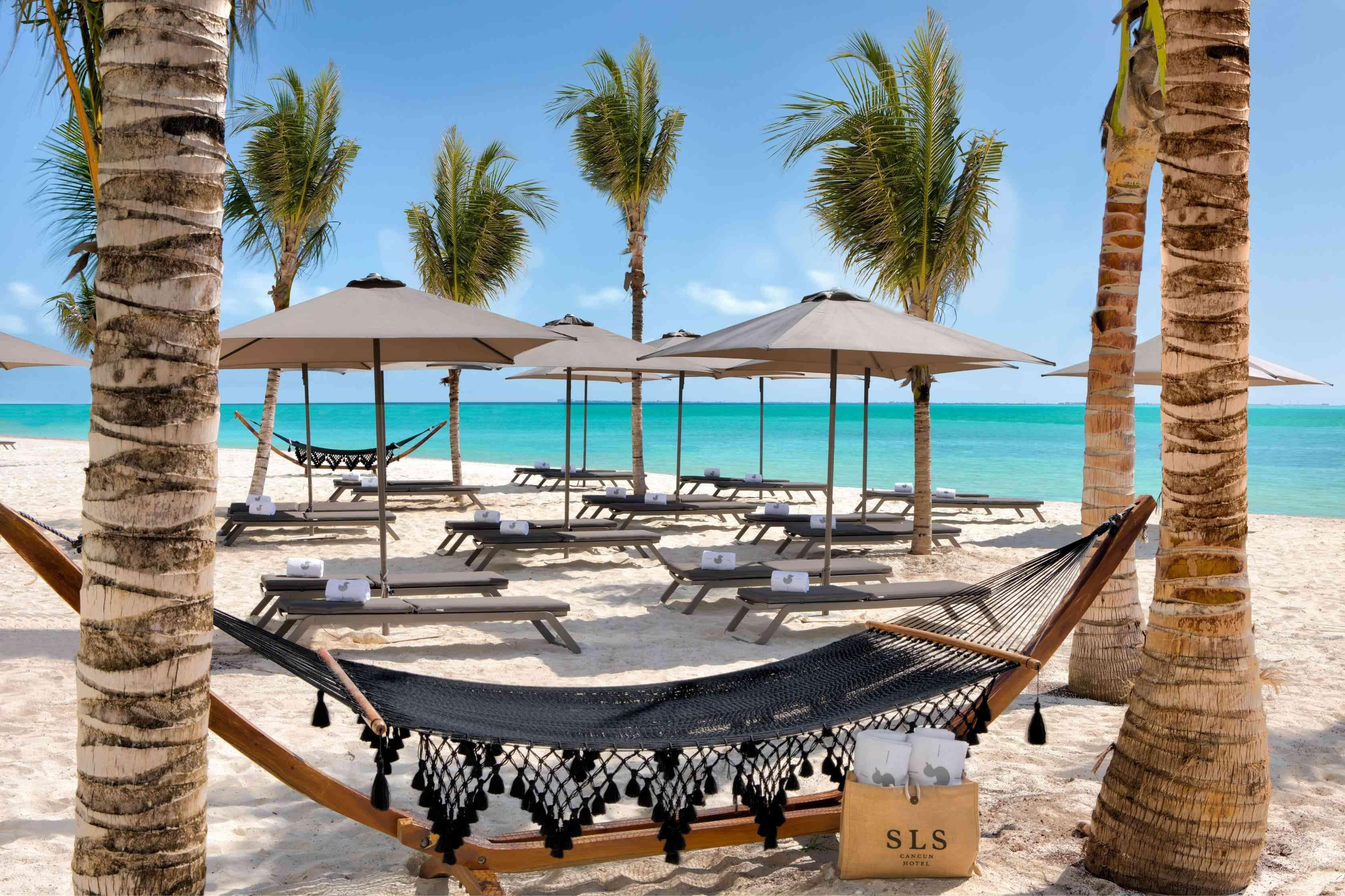 Sitting area on the beach with hammocks and umbrella covered chaise loungers
