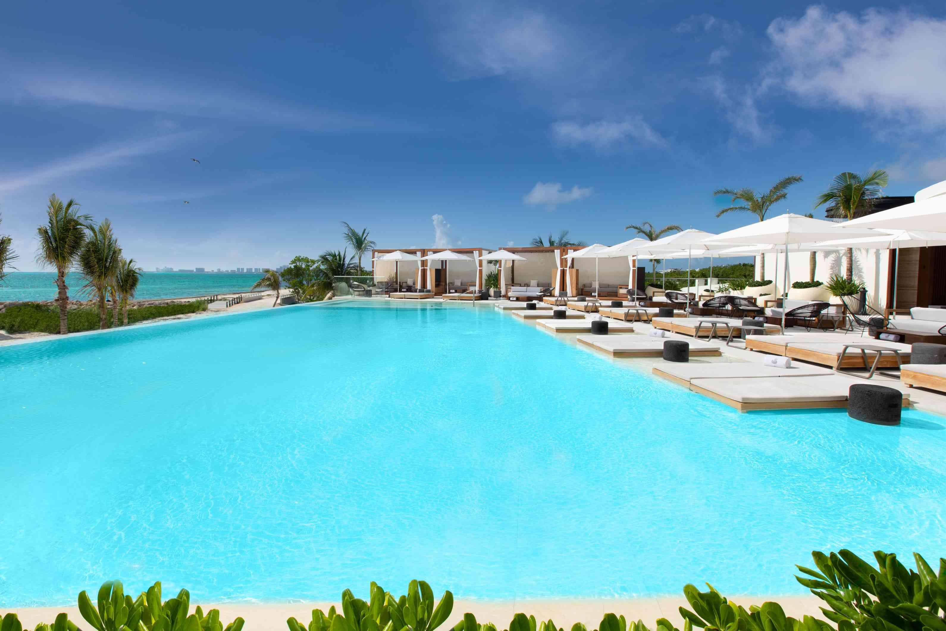 Clear blue pool with cabanas and tanning area along the side