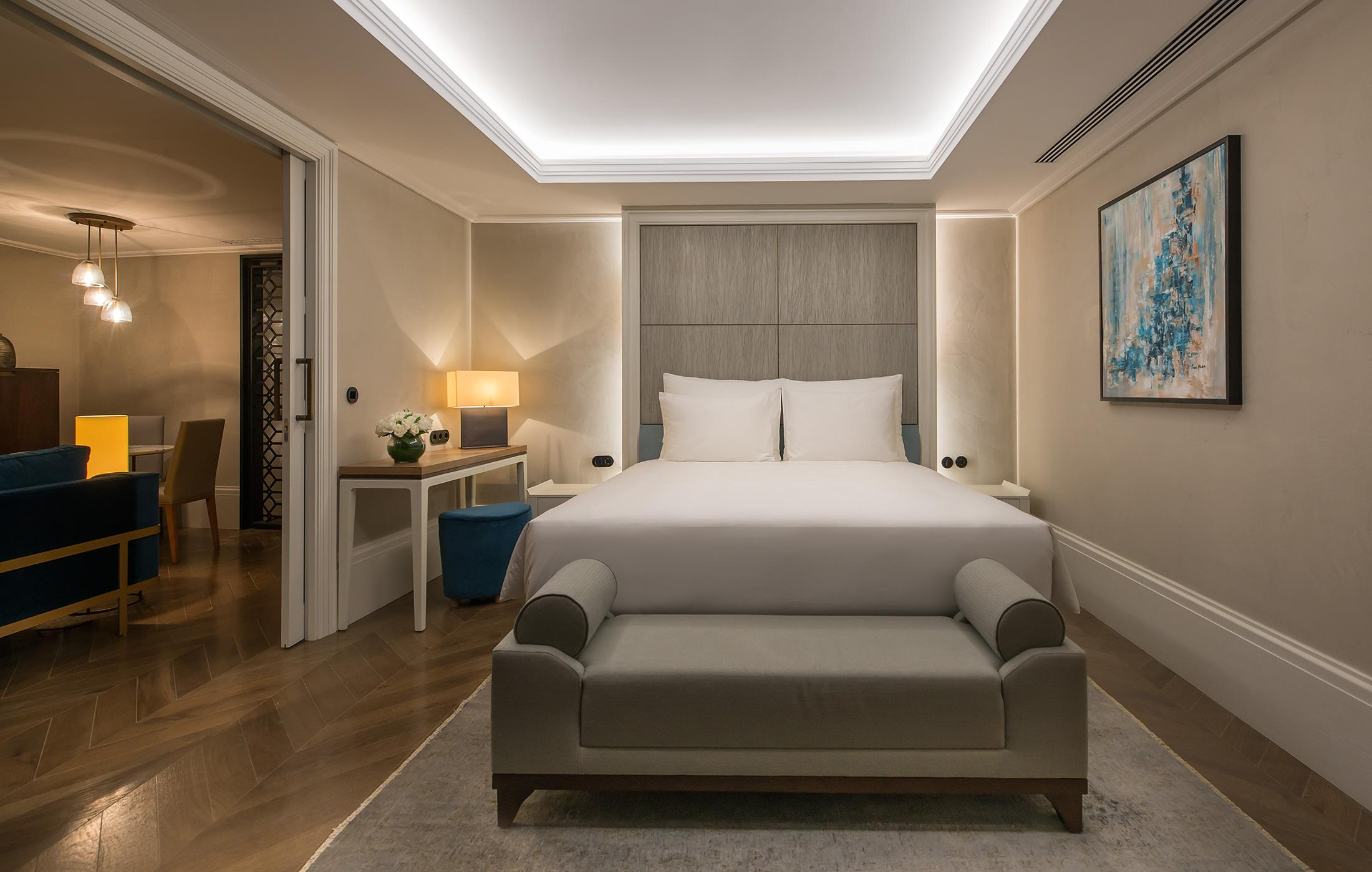 penthouse hotel bedroom with large bed and bench