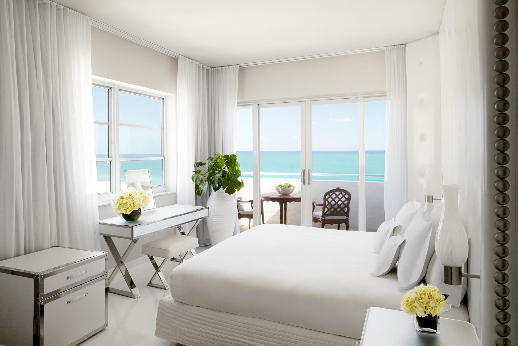 White bed in front of wall of windows with ocean view