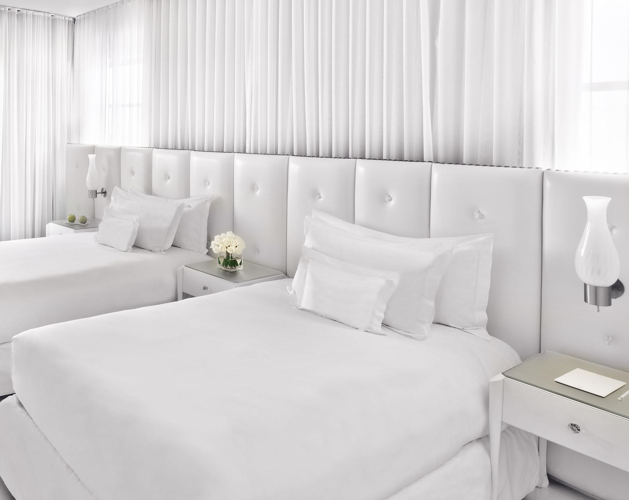 Two comfortable white beds in white room