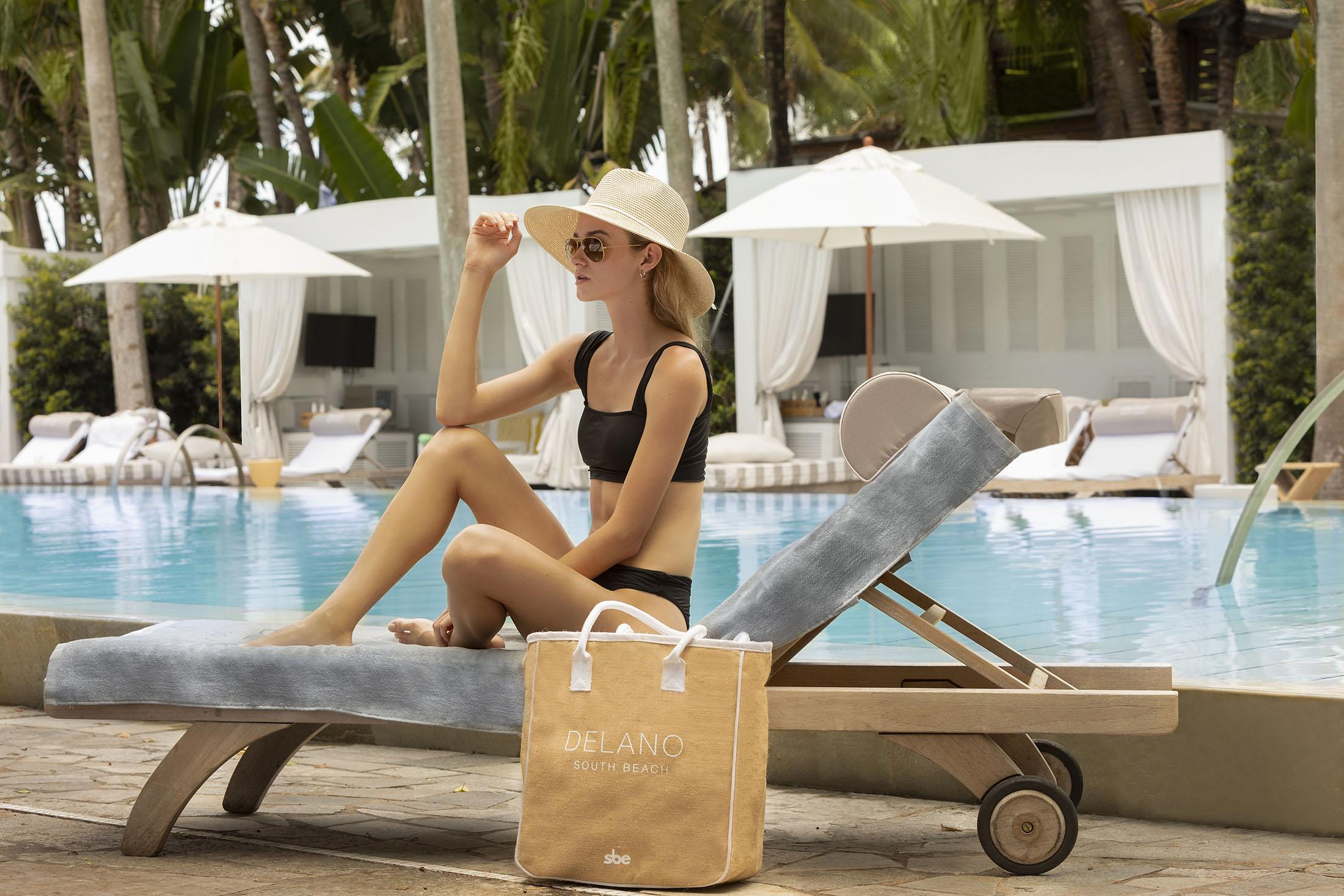 Woman in black swim suit and large hat lounges by pool