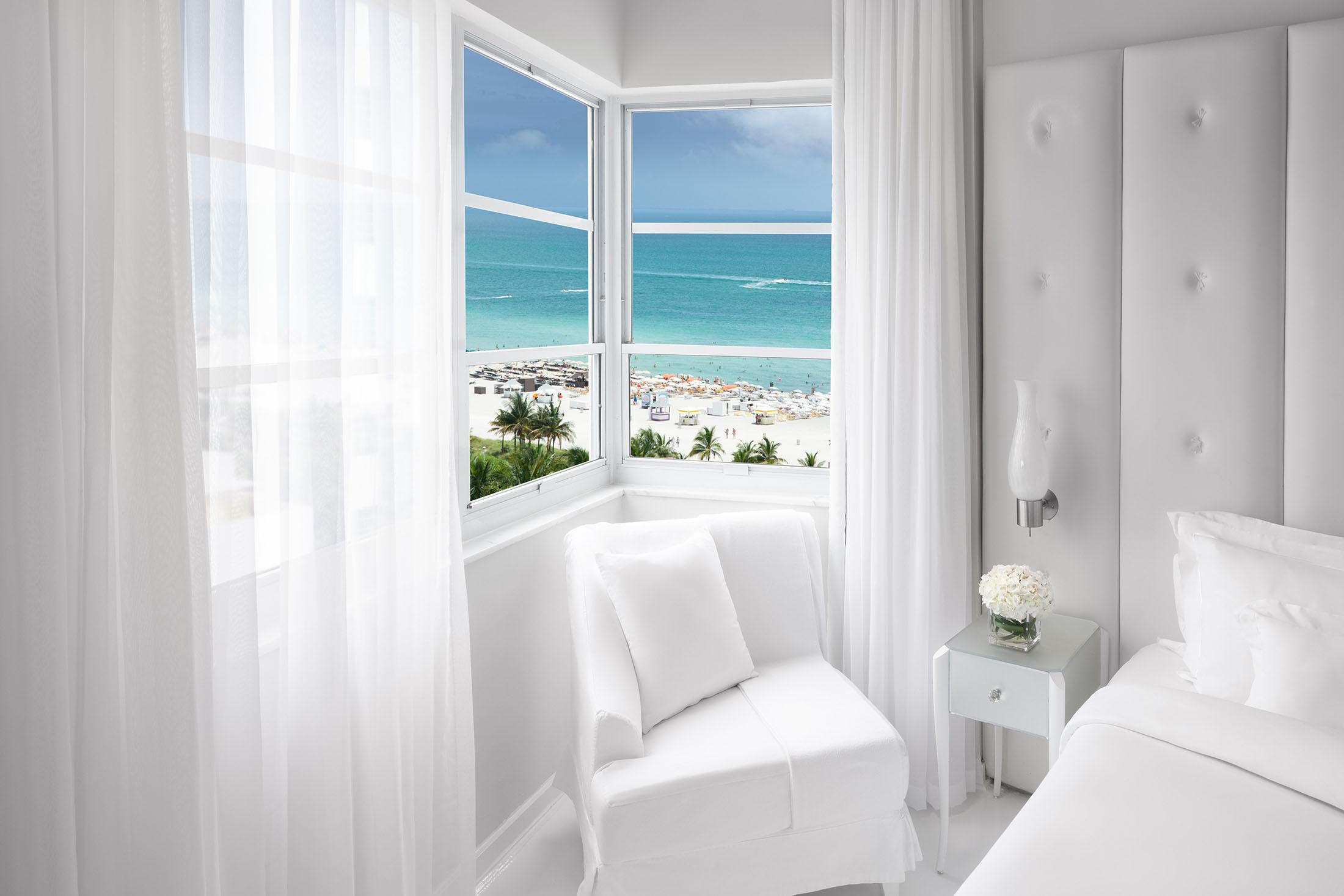 White chair in front of window with ocean view