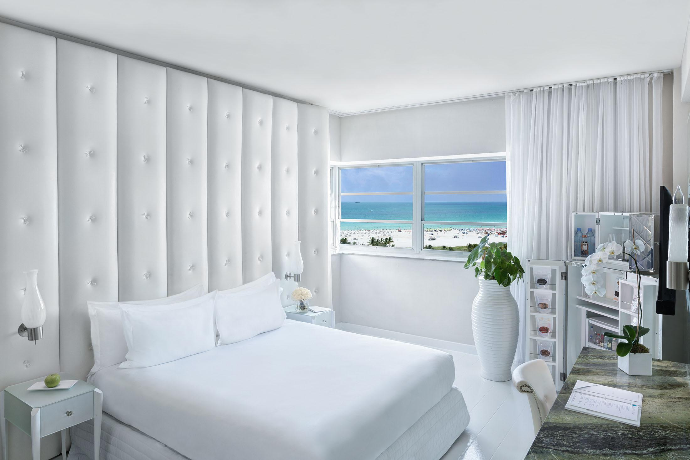 White bed in front of window with ocean view