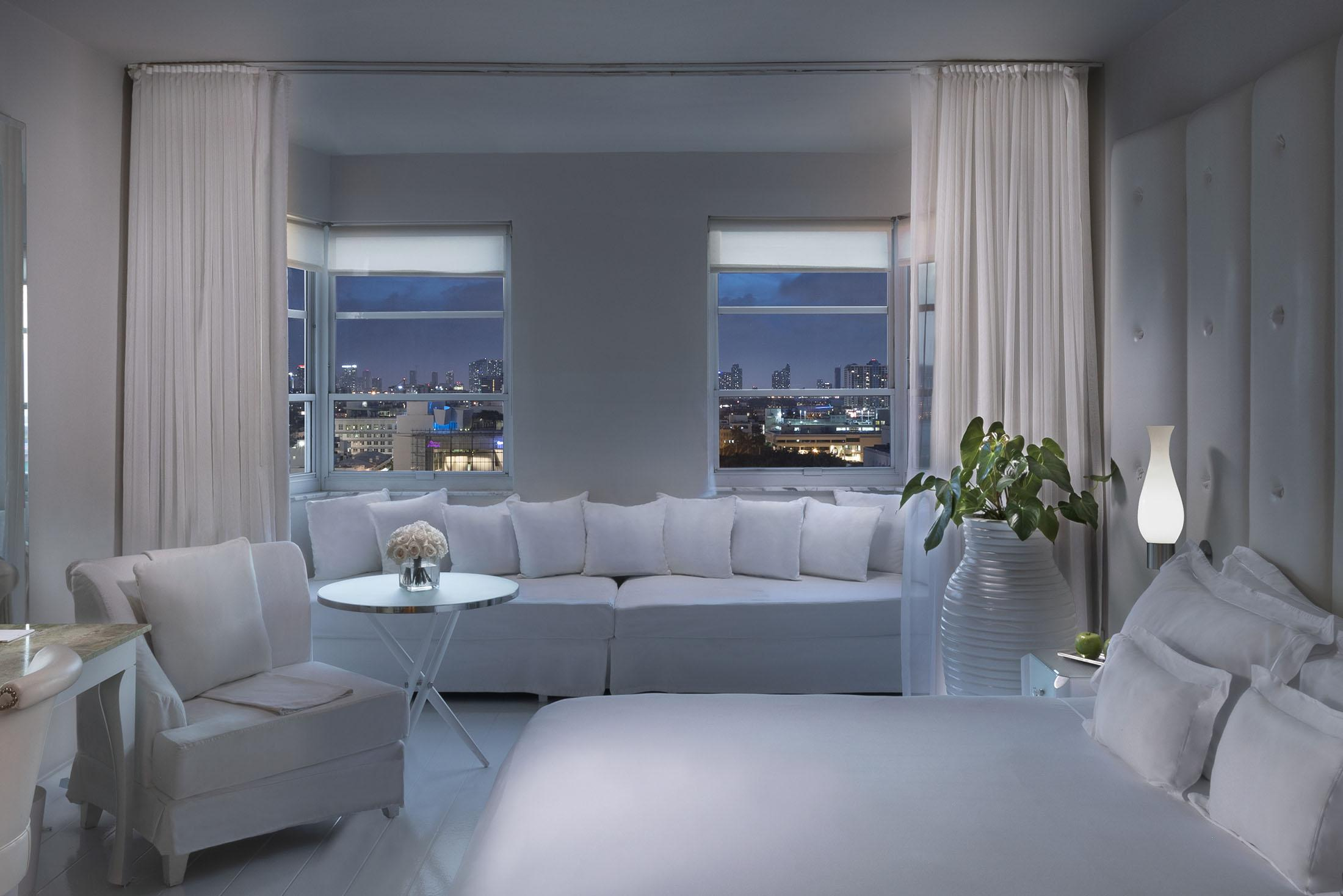 white bed and white sitting alcove in front of window with city view