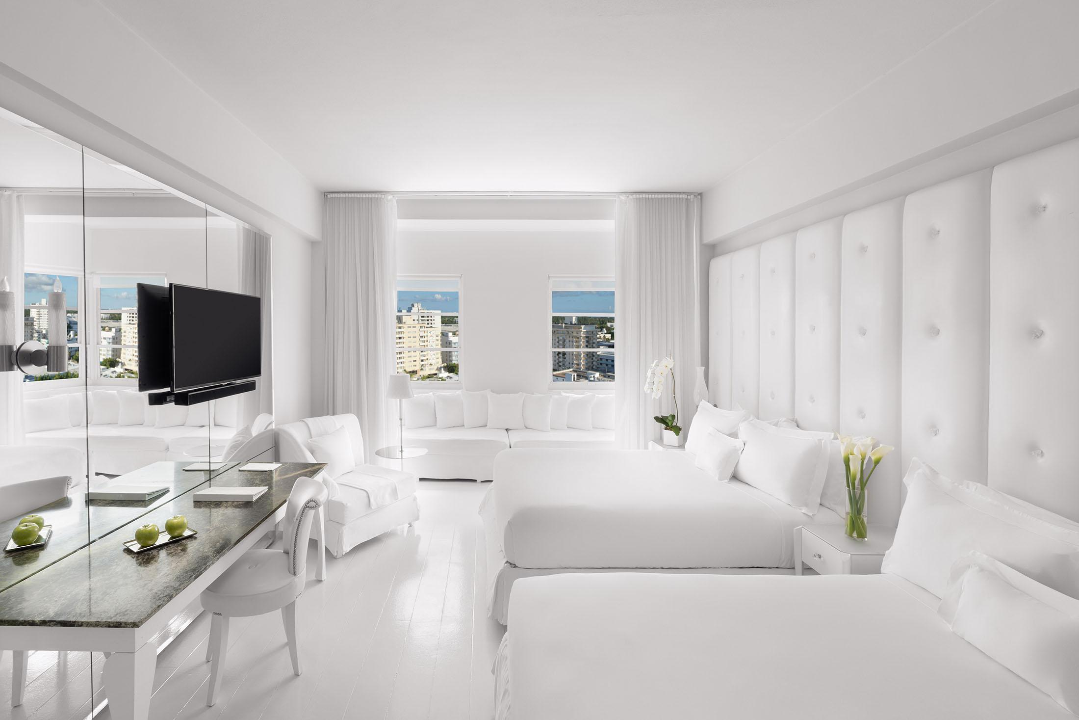 Two queen beds in a white room