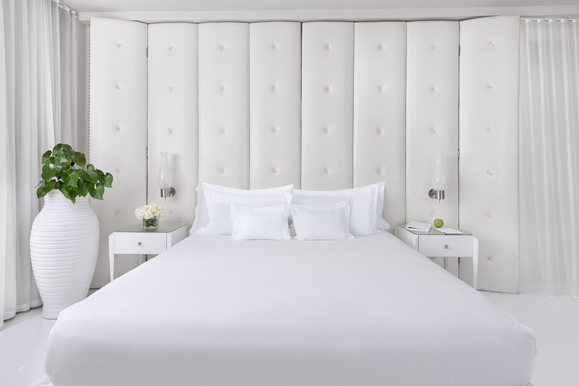 White bed in front of white panelled walls