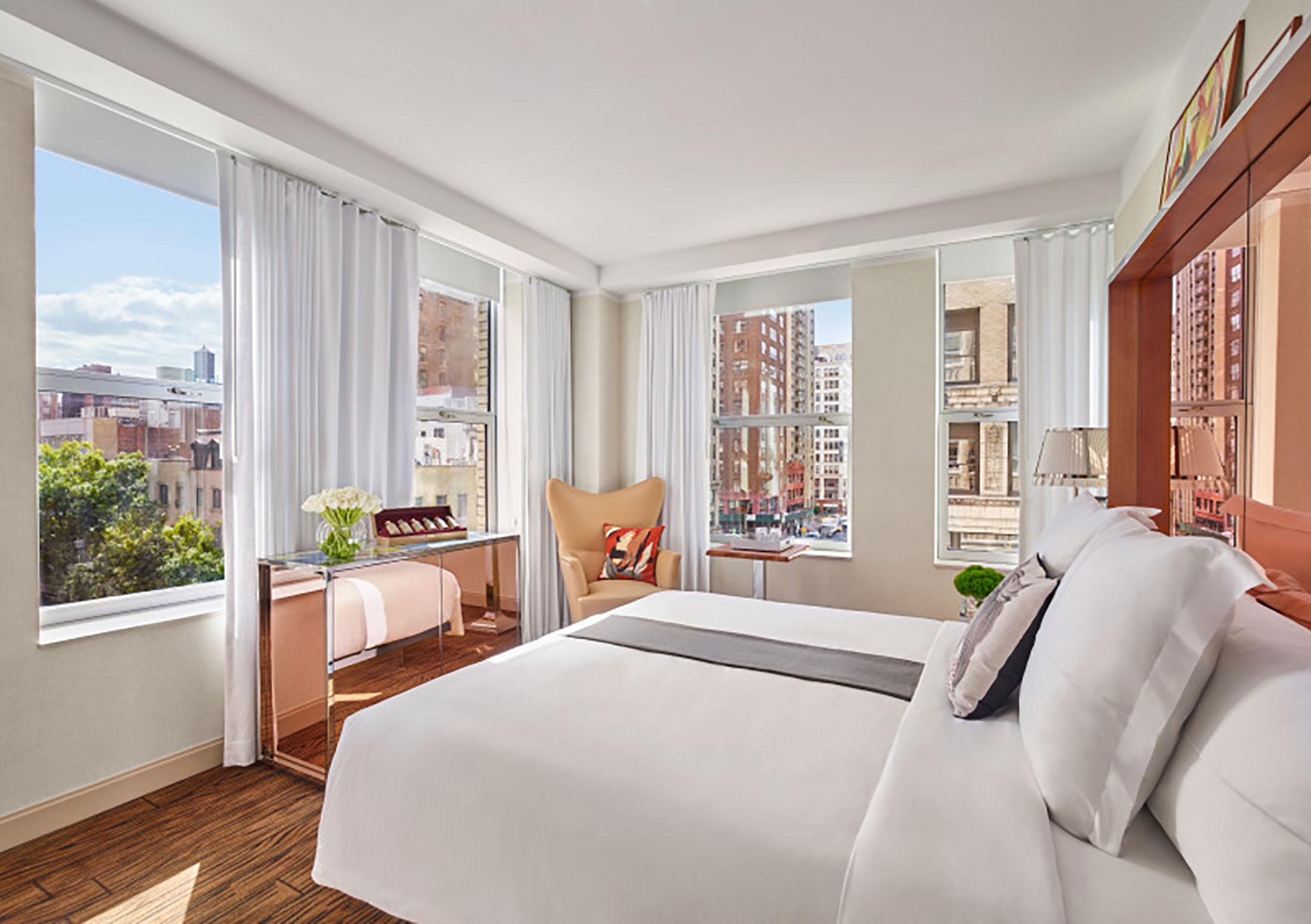 A bright hotel room overlooking the city