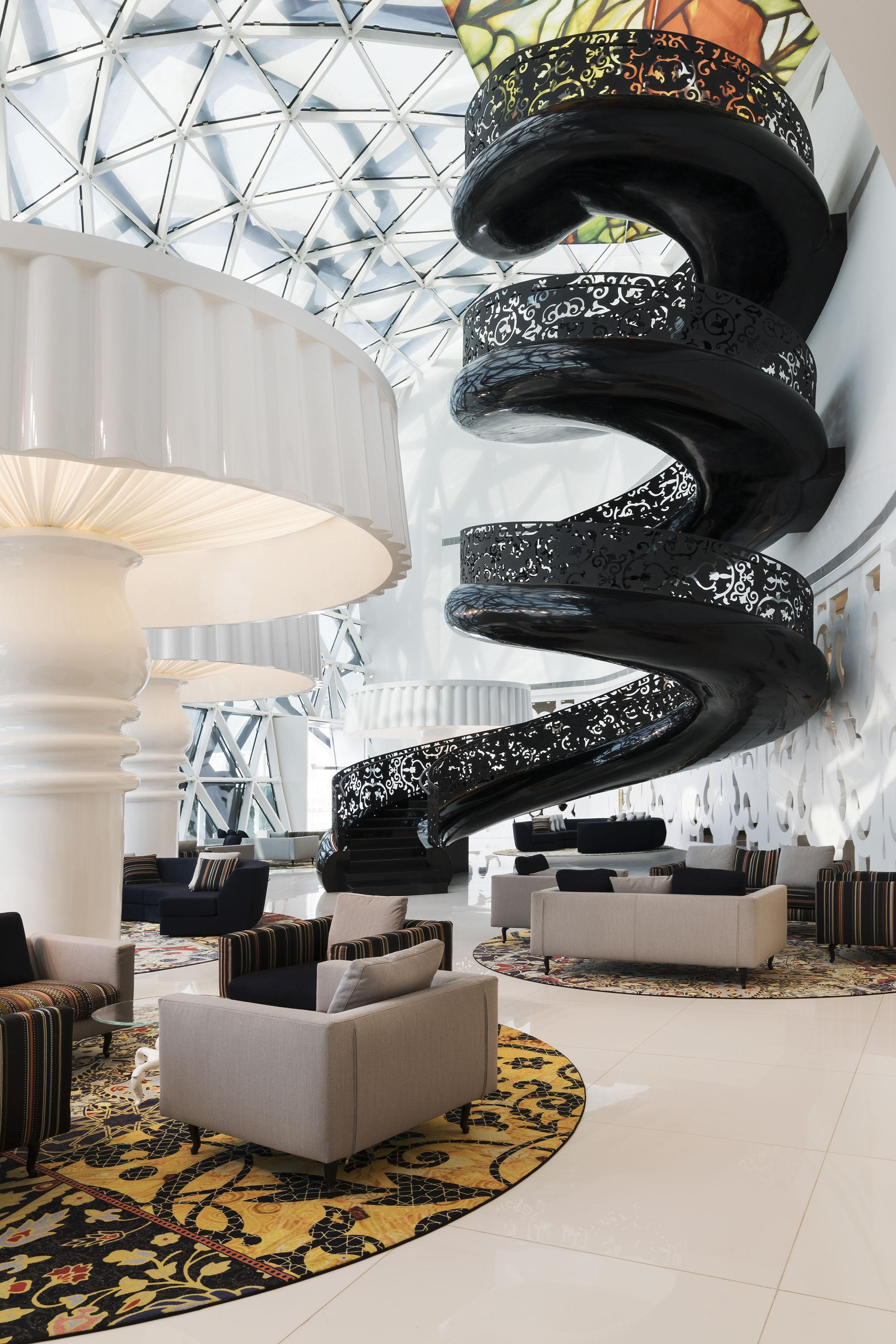 A brightly sit atrium with a black spiral staircase