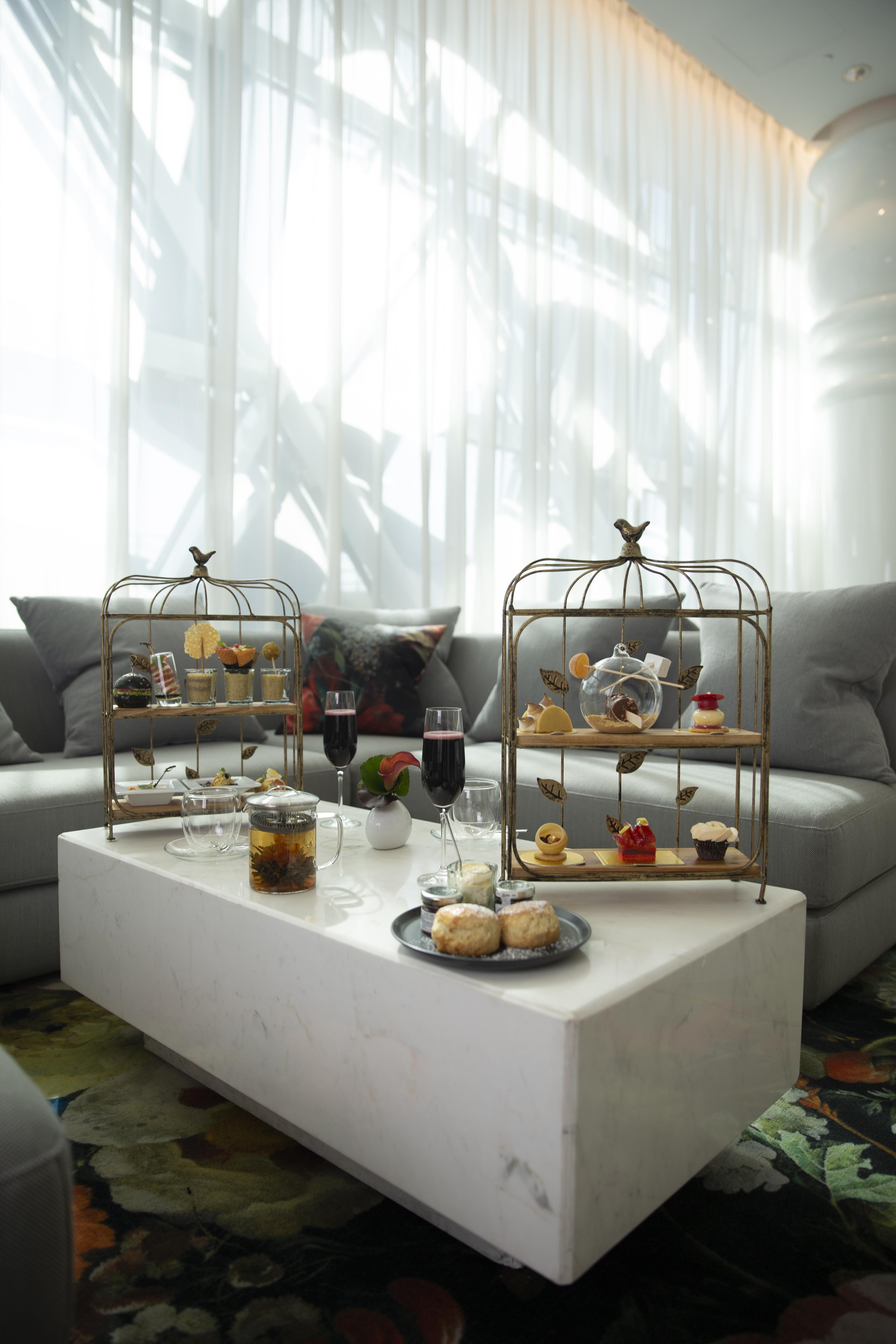 Afternoon high-tea set with elegant decorations and desserts.