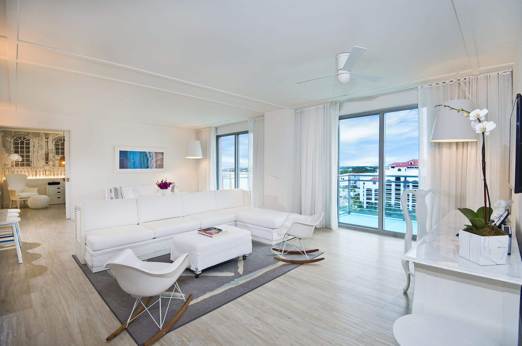 hotel room living space with white couch and chairs