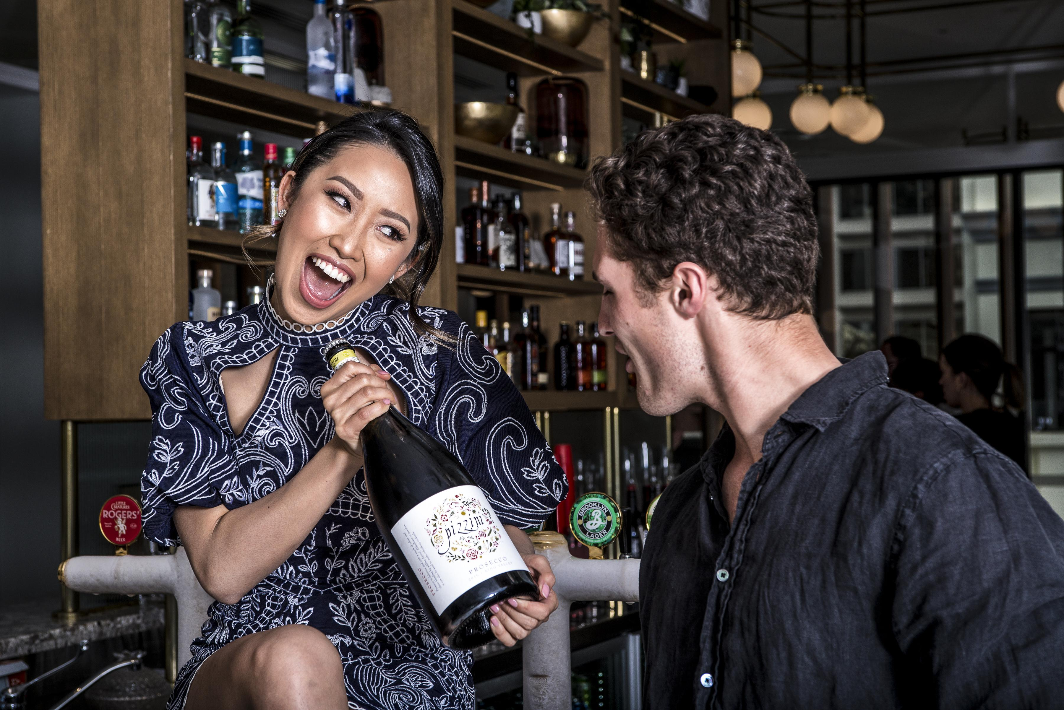 Photo of a woman smiling and showing a bottle of wine to a man.