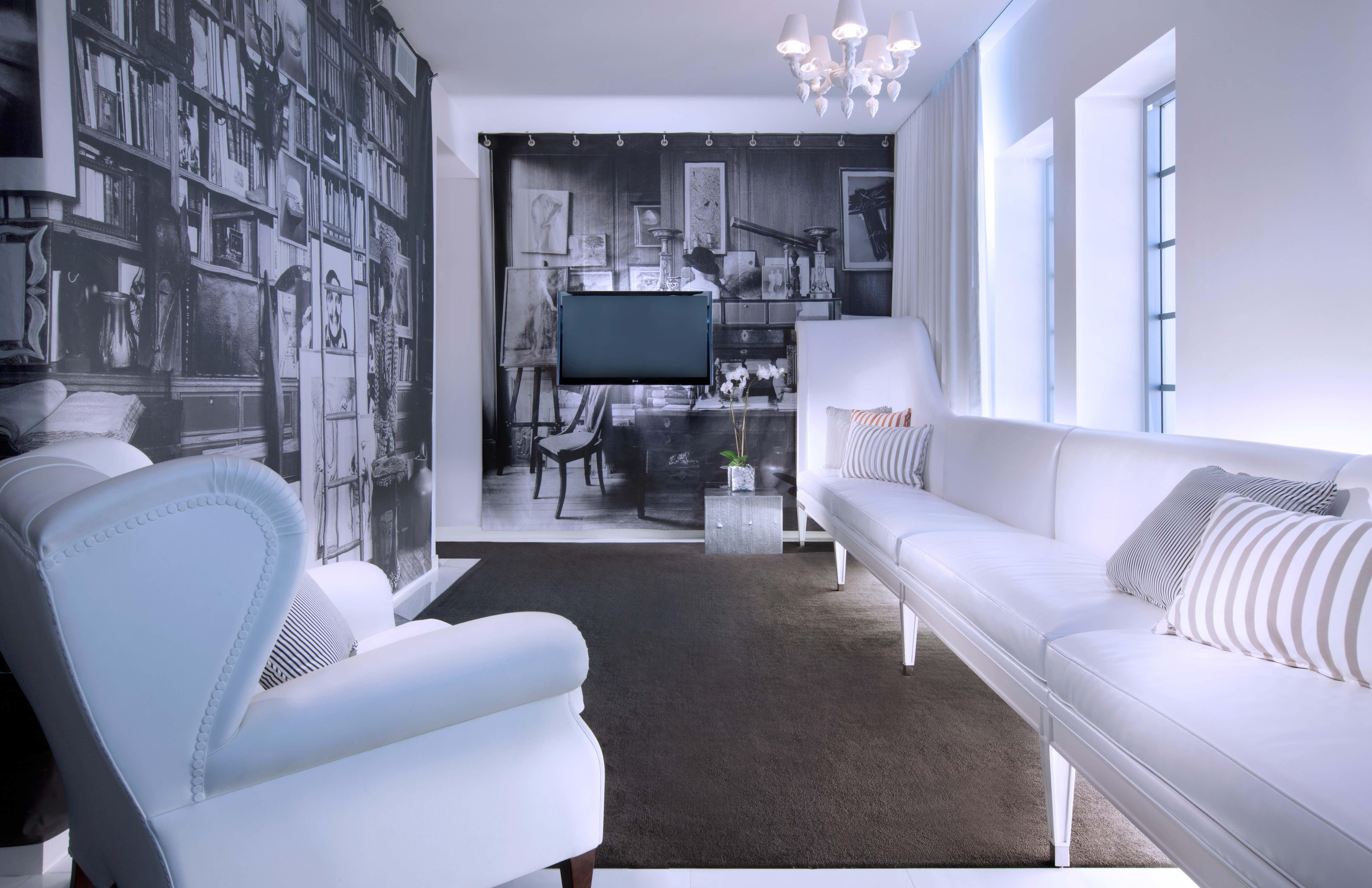 White couch and chair in front of black and white wallpaper
