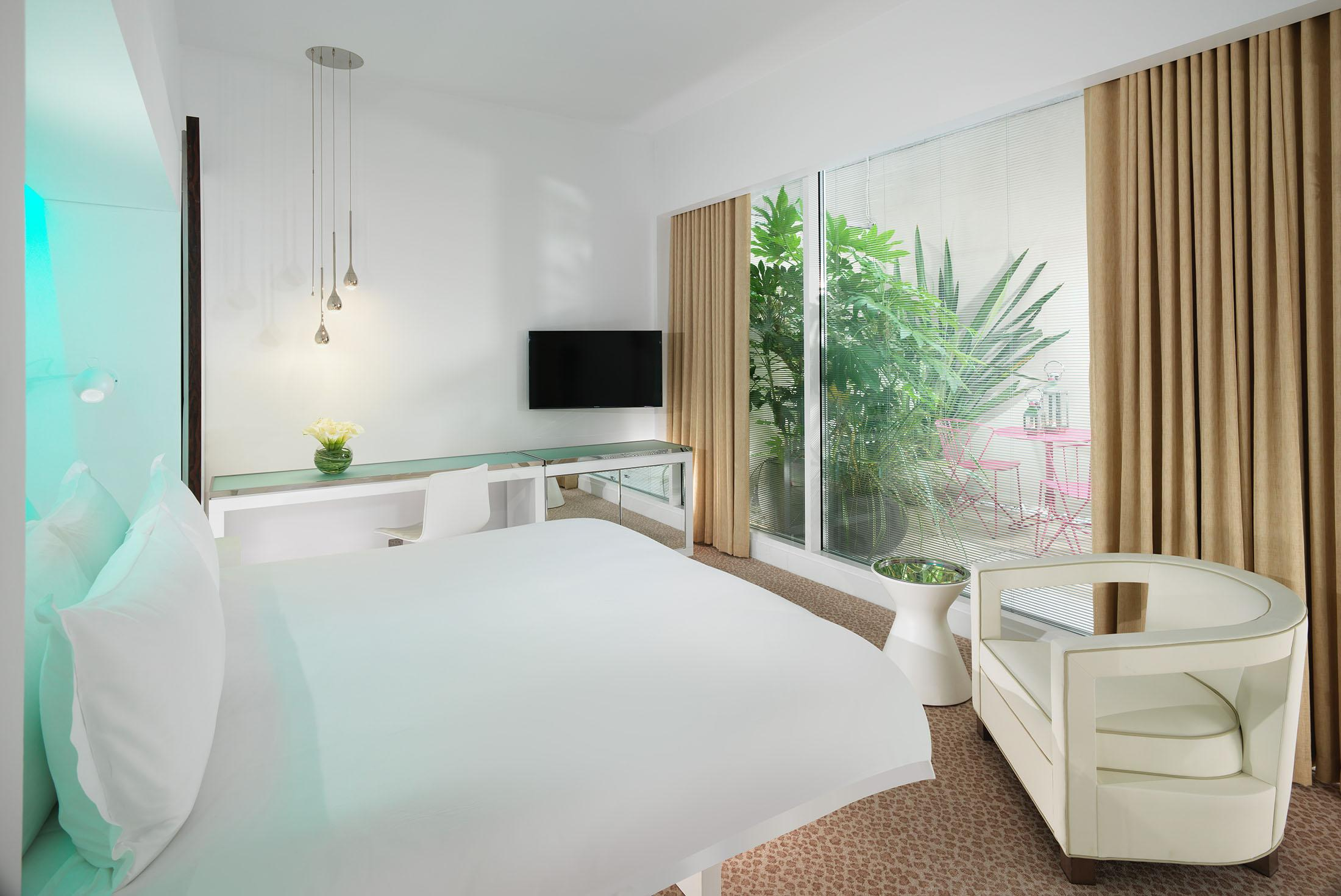 deluxe garden hotel room with bed and plants