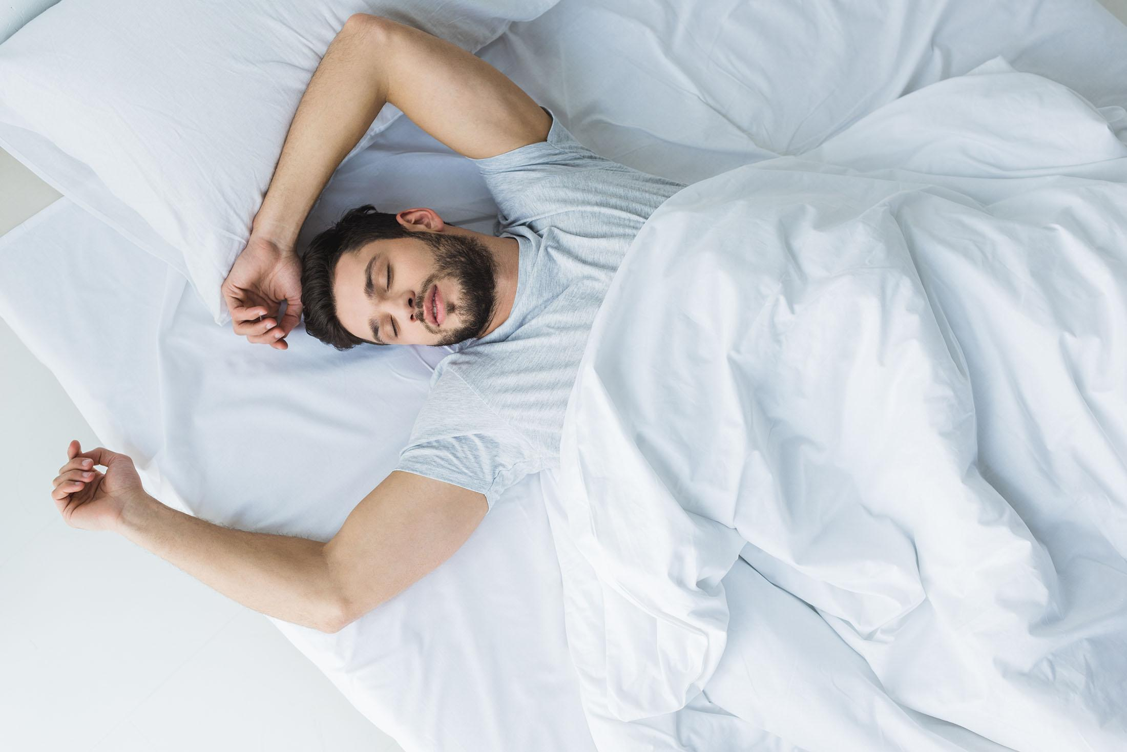 man asleep in bed with his arms over his head