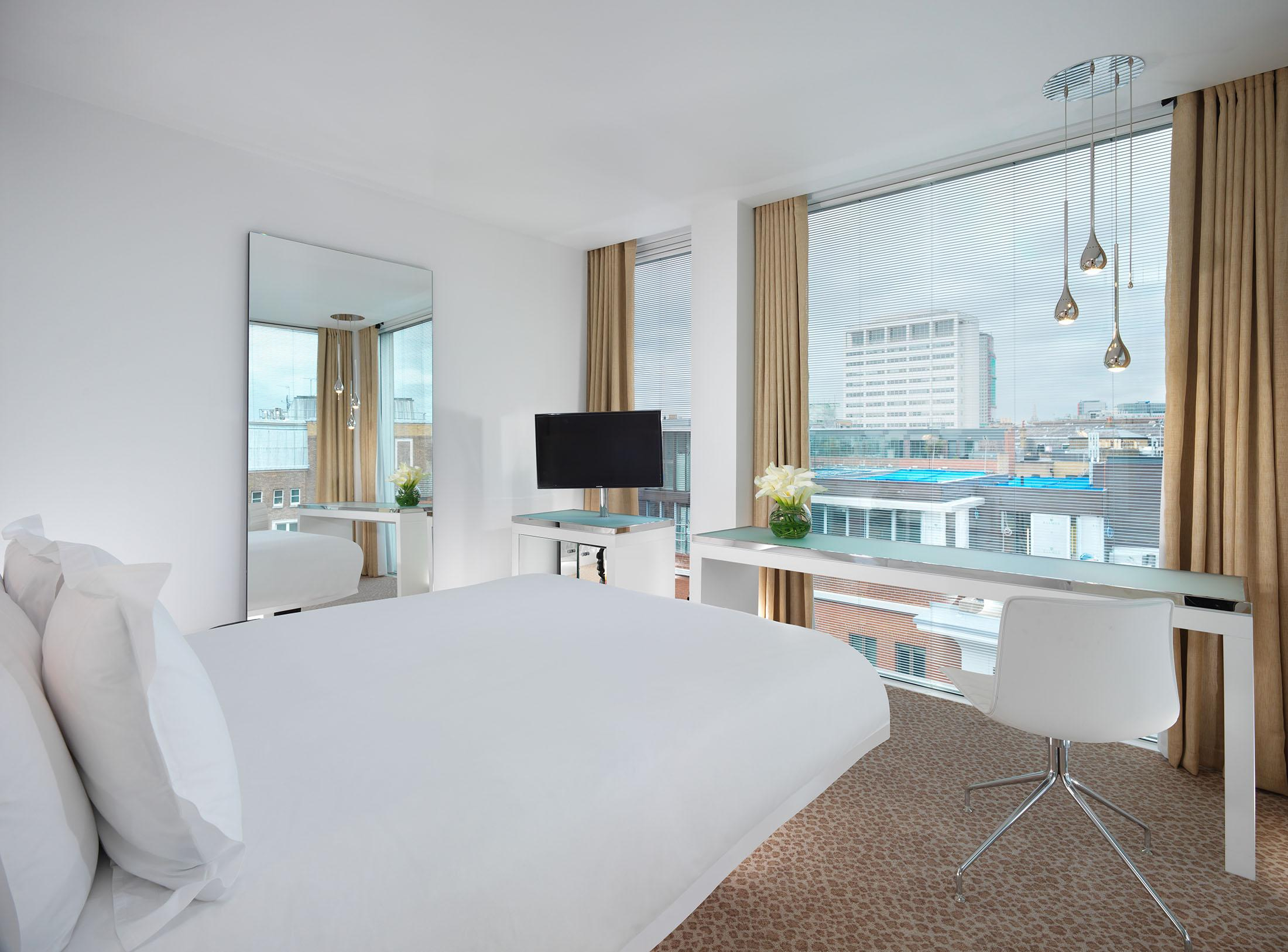 hotel room with bed and desk overlooking the city