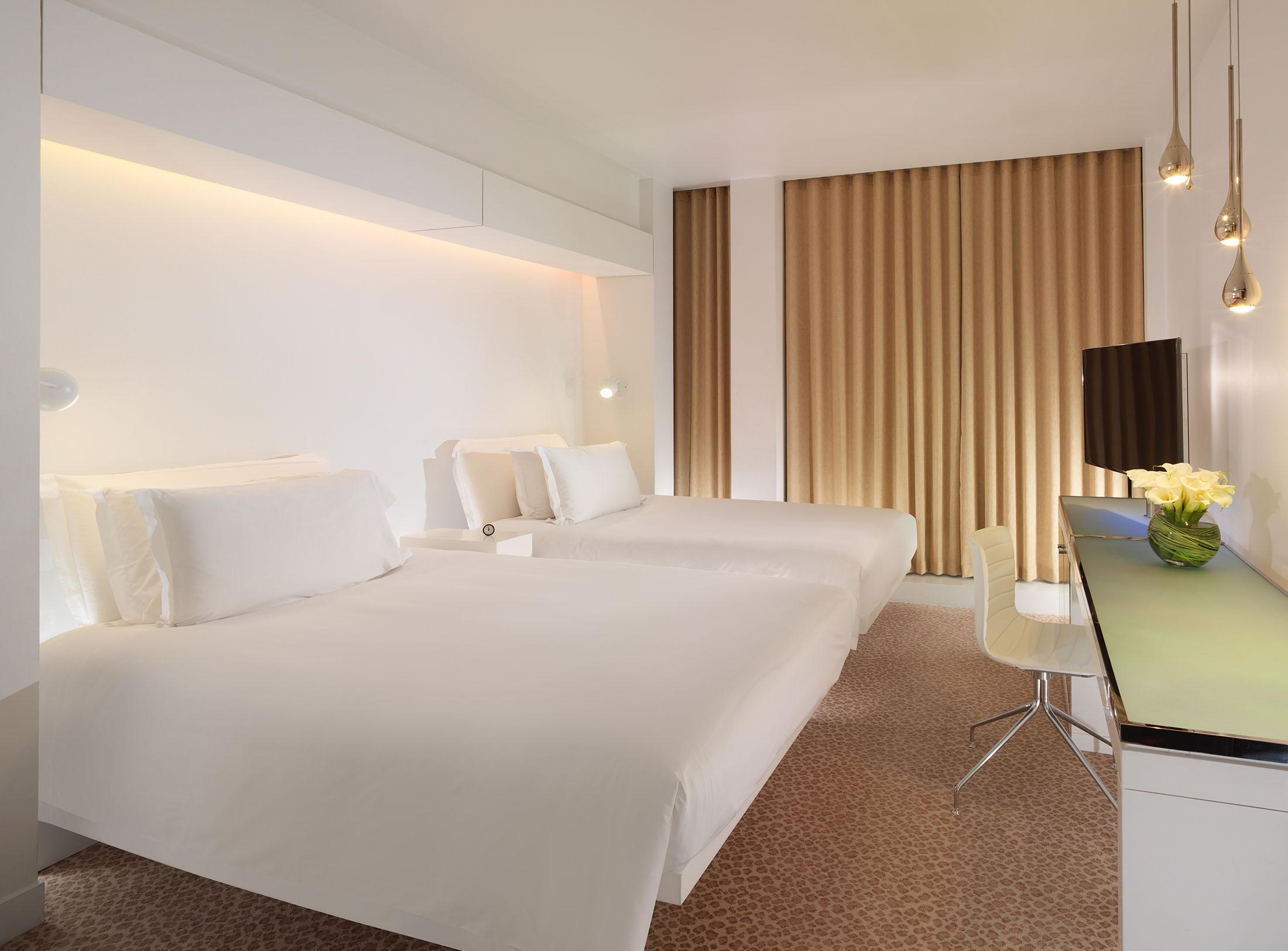 hotel bedroom with two beds all in white