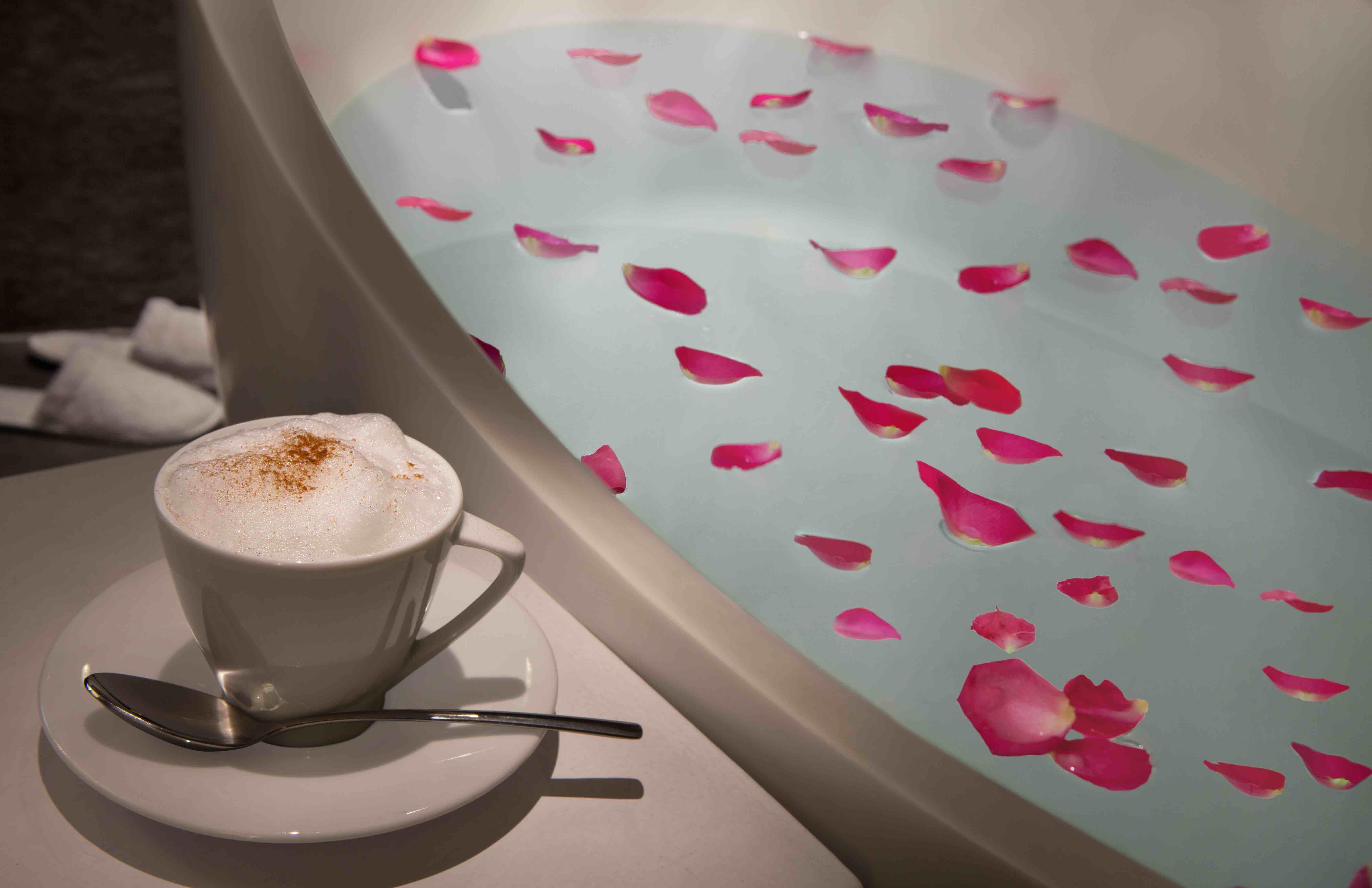 Coffee next to a bathtub with flower petals