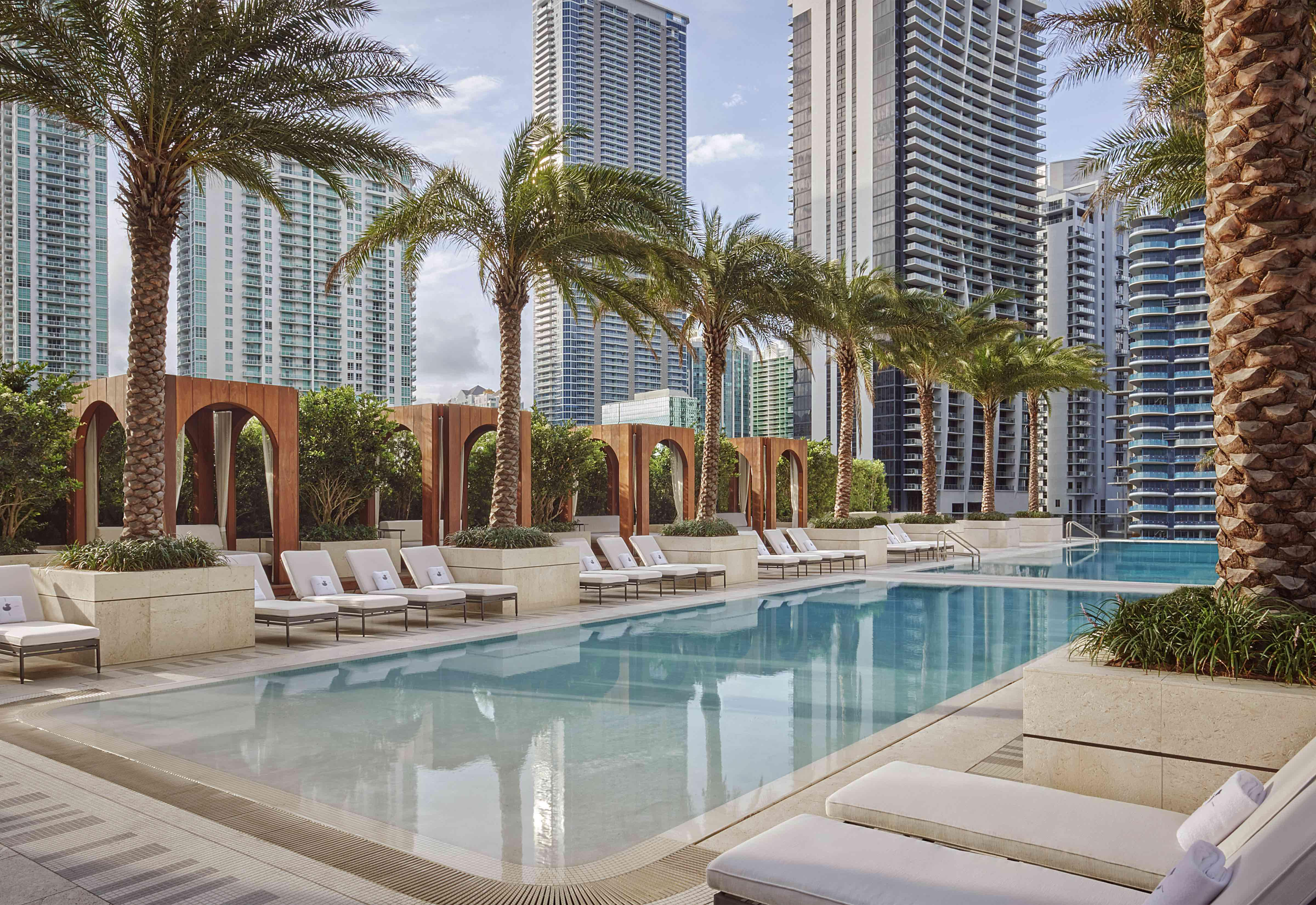 pool surrounded by white lounge chairs and palm trees