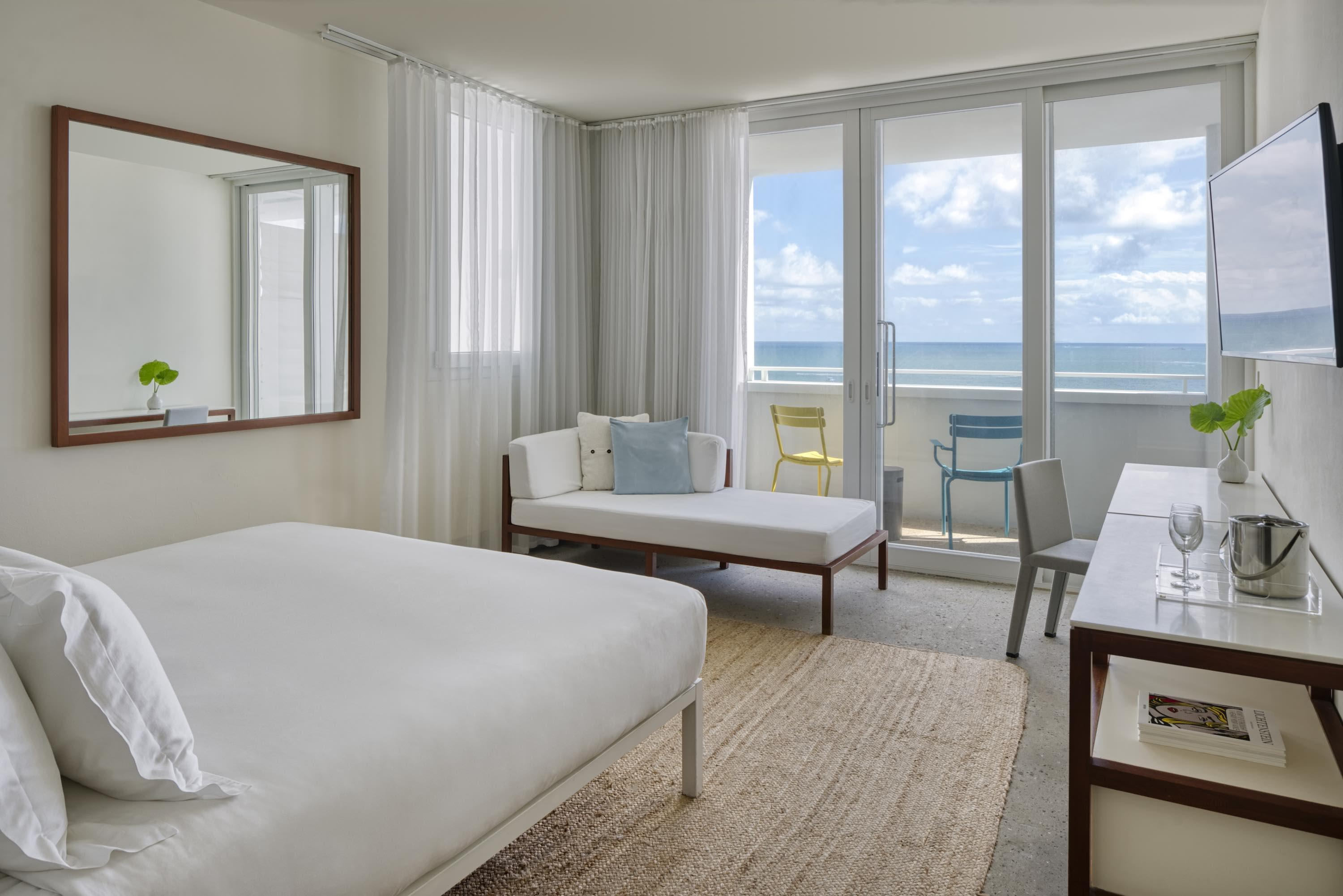 white hotel room with bed and sitting area in front of large windows