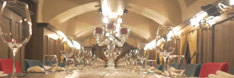 Close up view of wine glasses along a dining table.