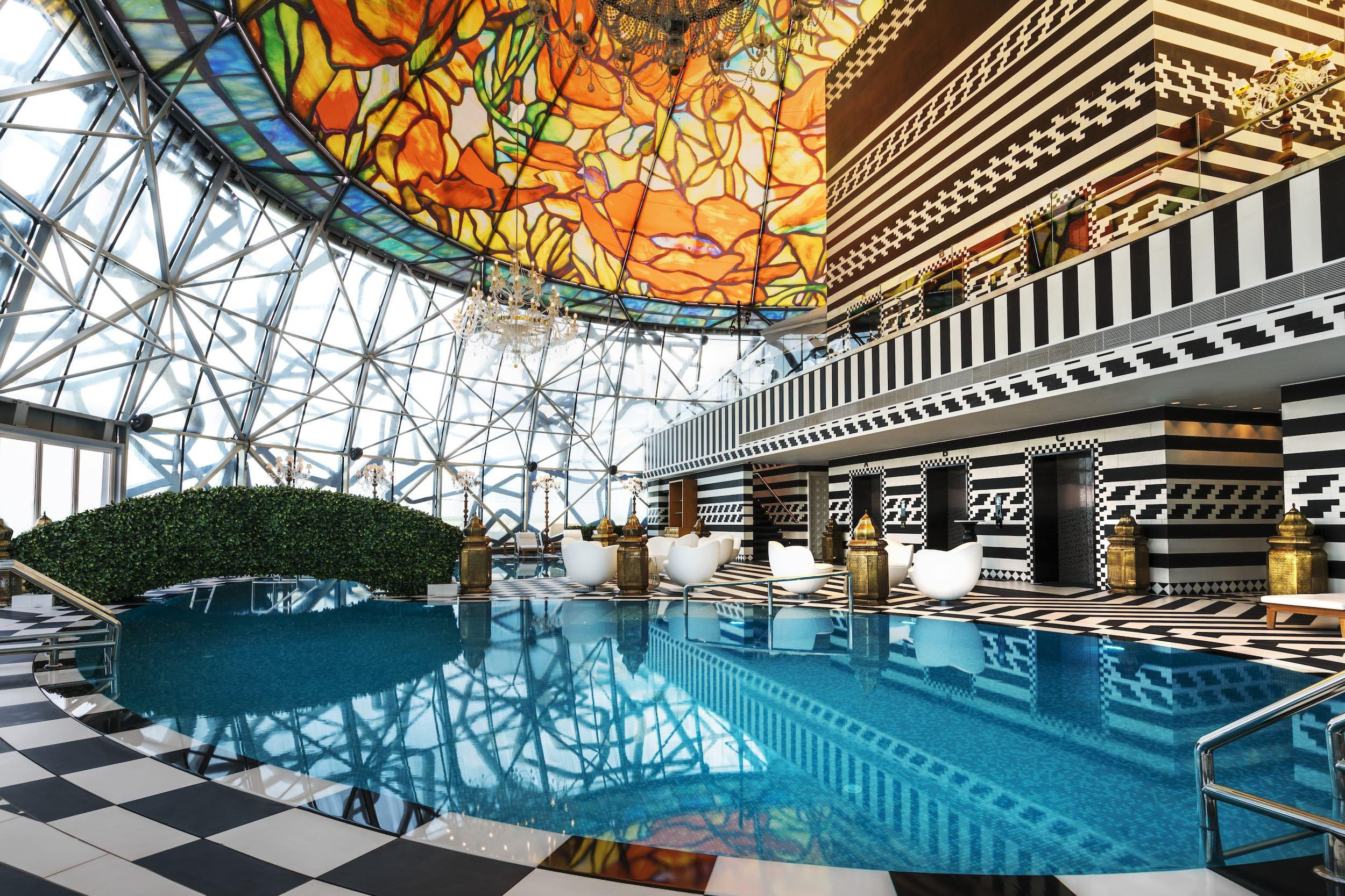 Pool surrounded by black and white floor and colorful glass ceiling