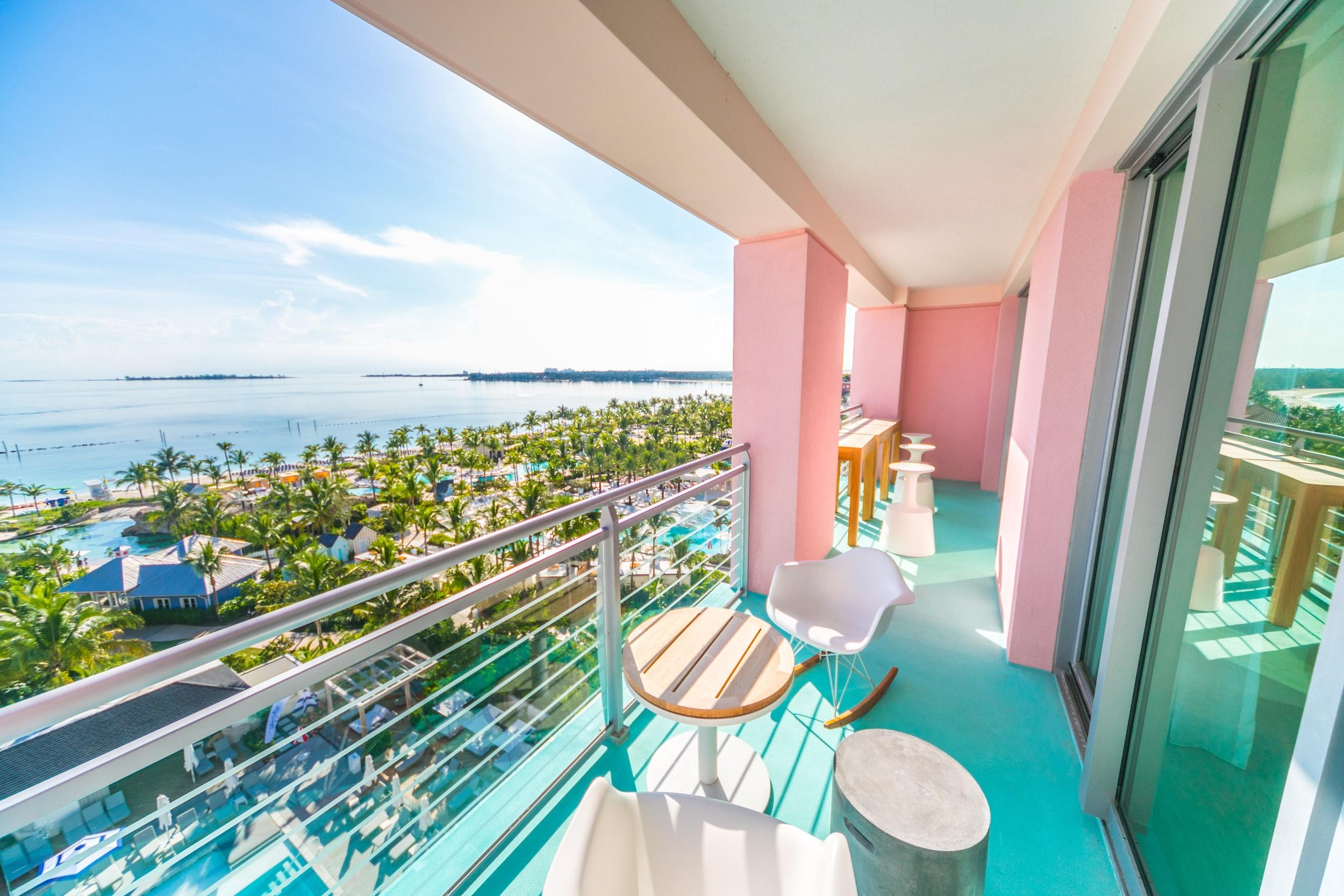 Pink and turquoise balcony overlooking tropical ocean