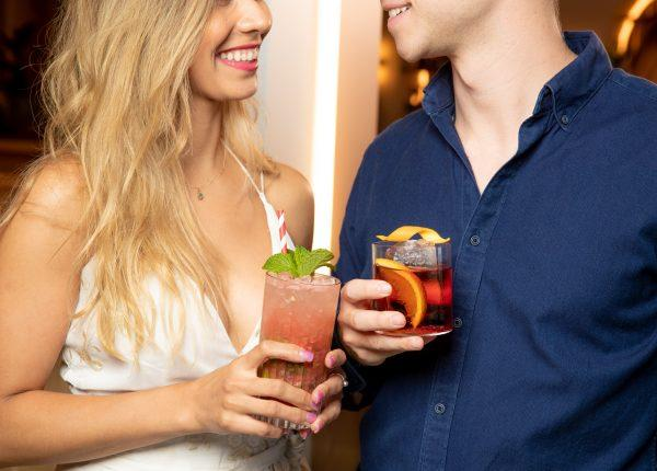 man and woman smiling holding drinks