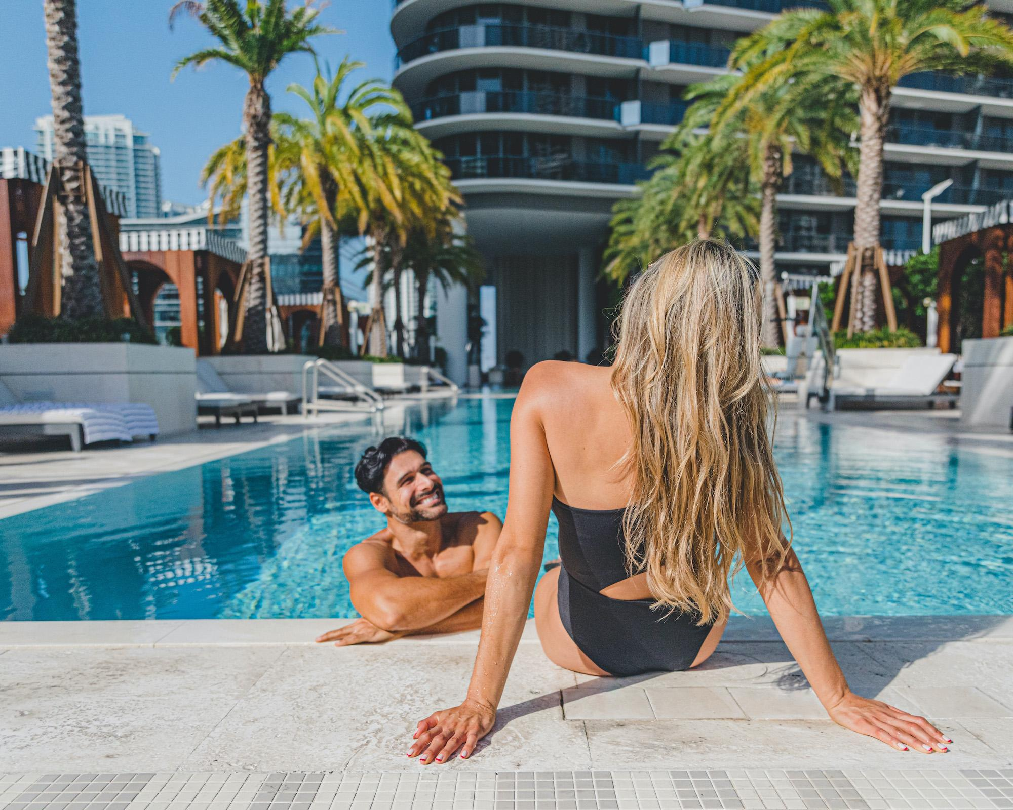 man and woman smiling poolside