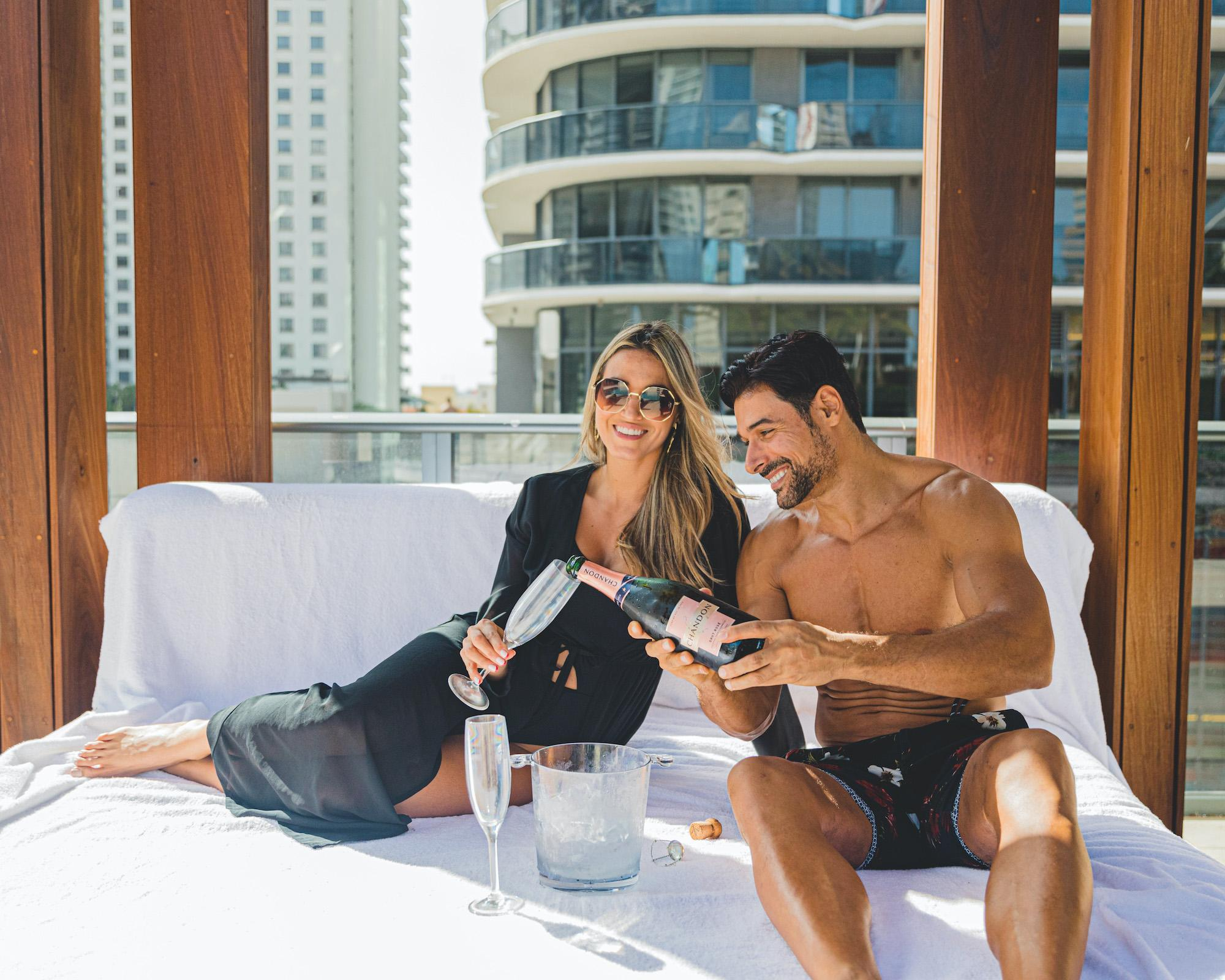 couple sitting on bed pouring champagne